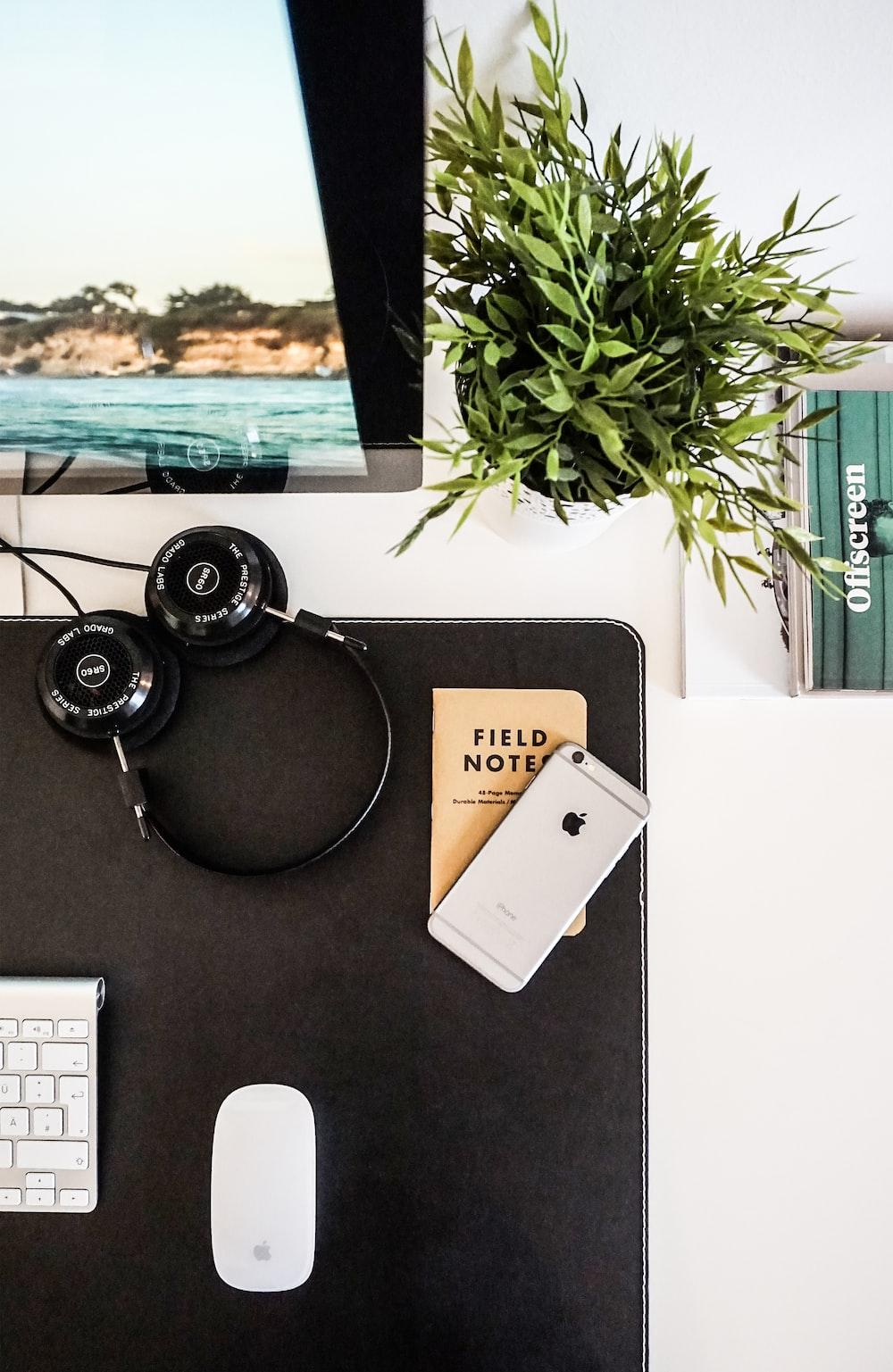 black headphones beside space gray iPhone on brown table