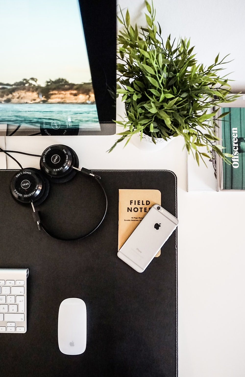 black headphones beside space gray iPhone on brown table
