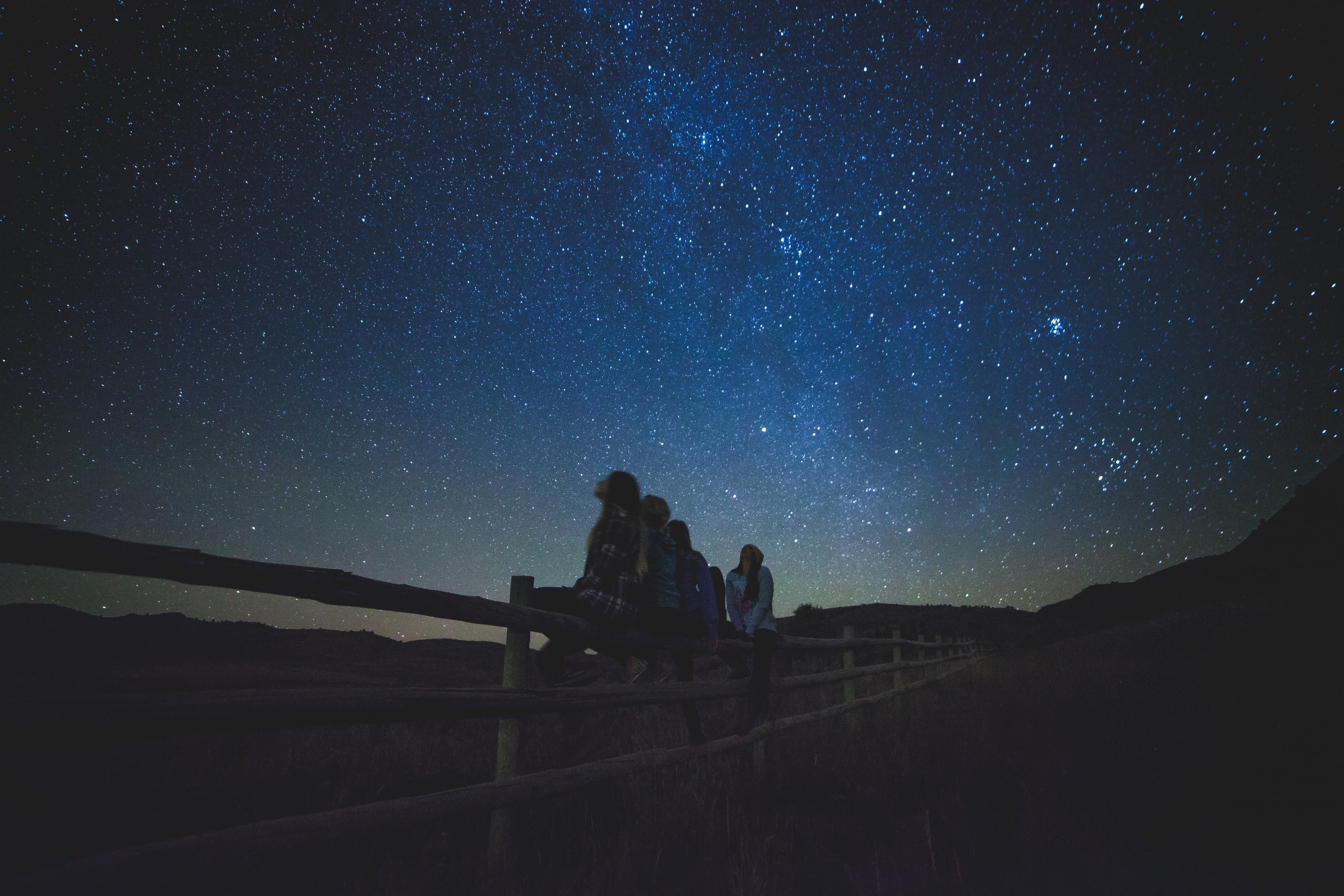 several women sitting on fence watching milky way