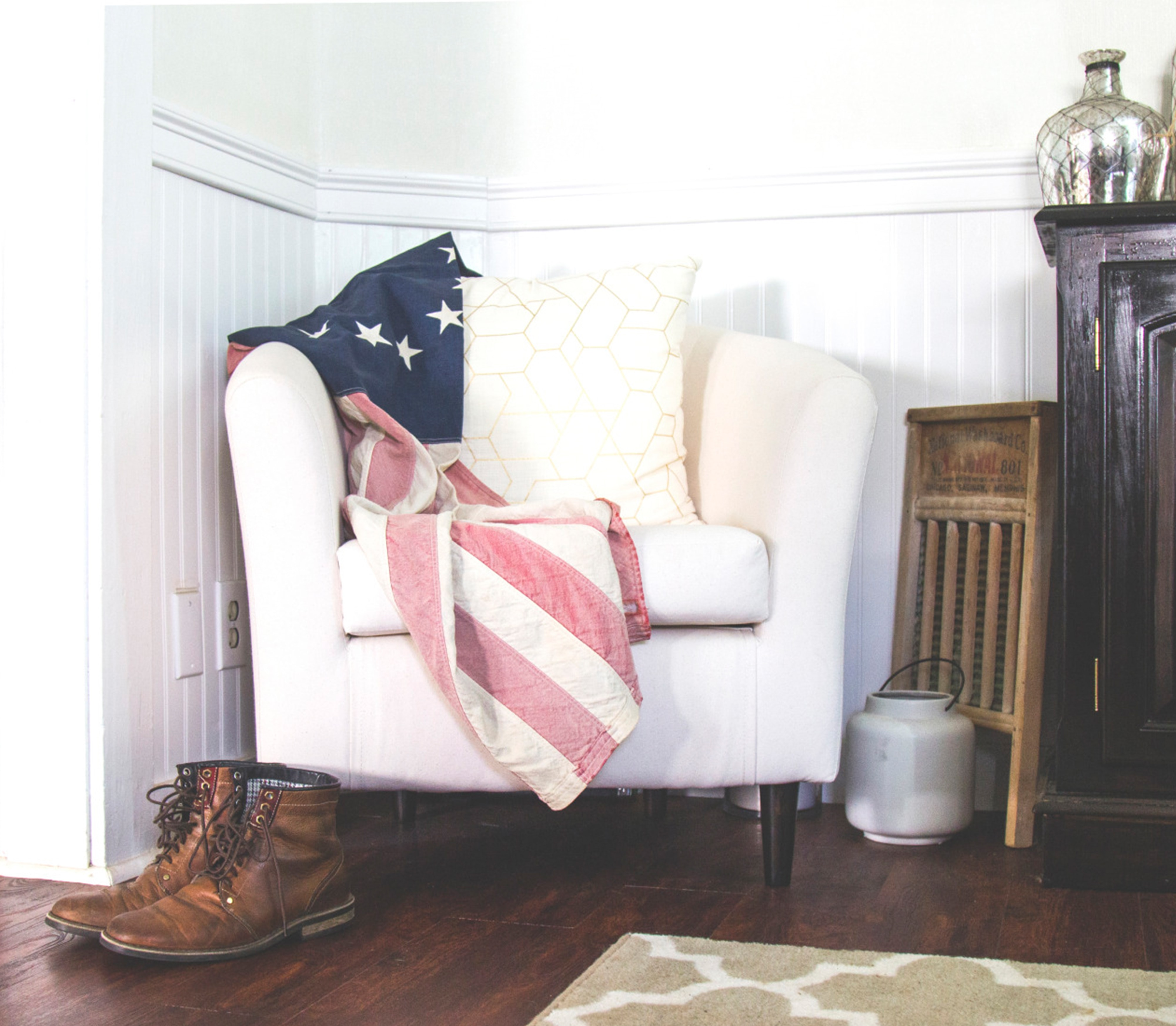 US flag and white throw pillow on white fabric sofa chair in room