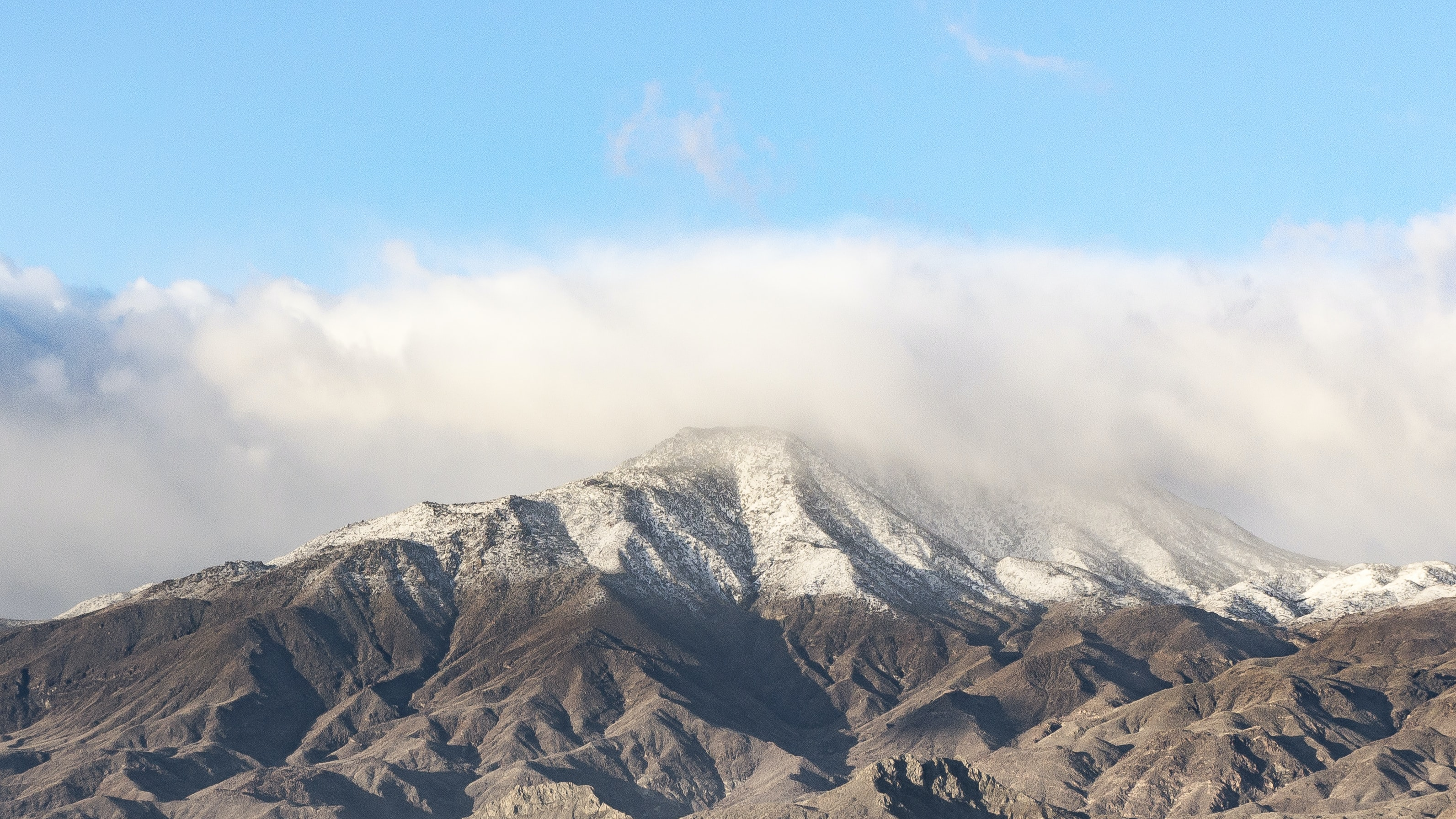 A scenic view of a snow covered mountain top with fog and a clear blue sky in Indio.