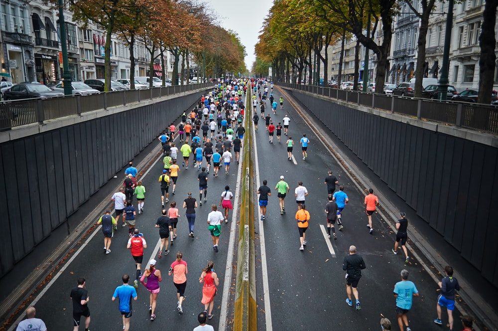 A large group of people running in a marathon in the middle of a street in Brussels