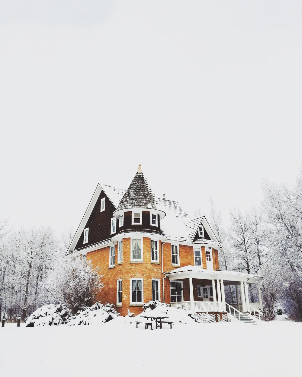 An elegant house with a turret covered in snow in winter