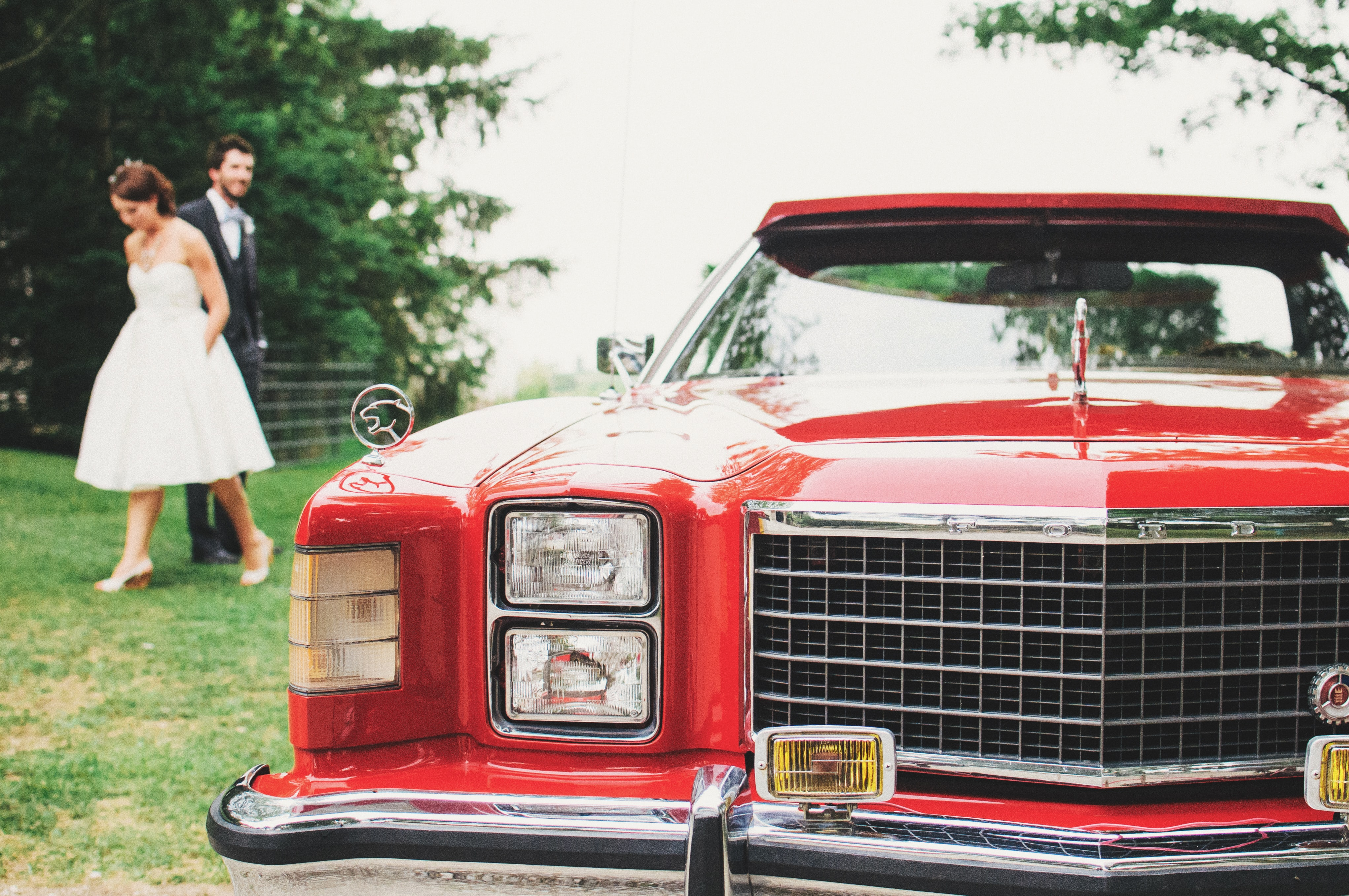 Retro red car at wedding with bride and groom in background