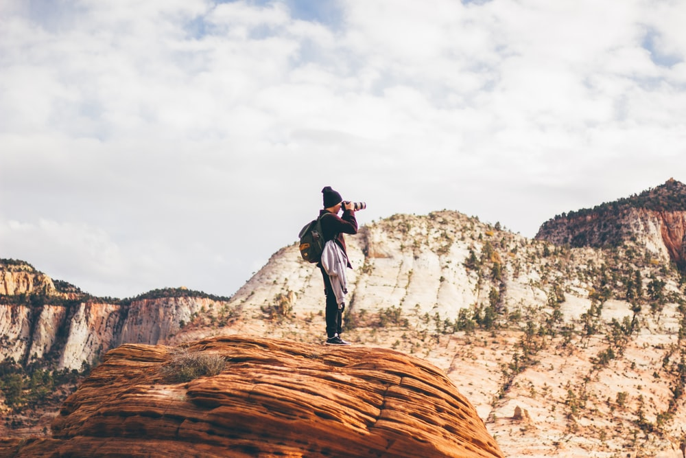 man wearing black jacket holding DSLR camera while taking photo standing on brown cliff during day time