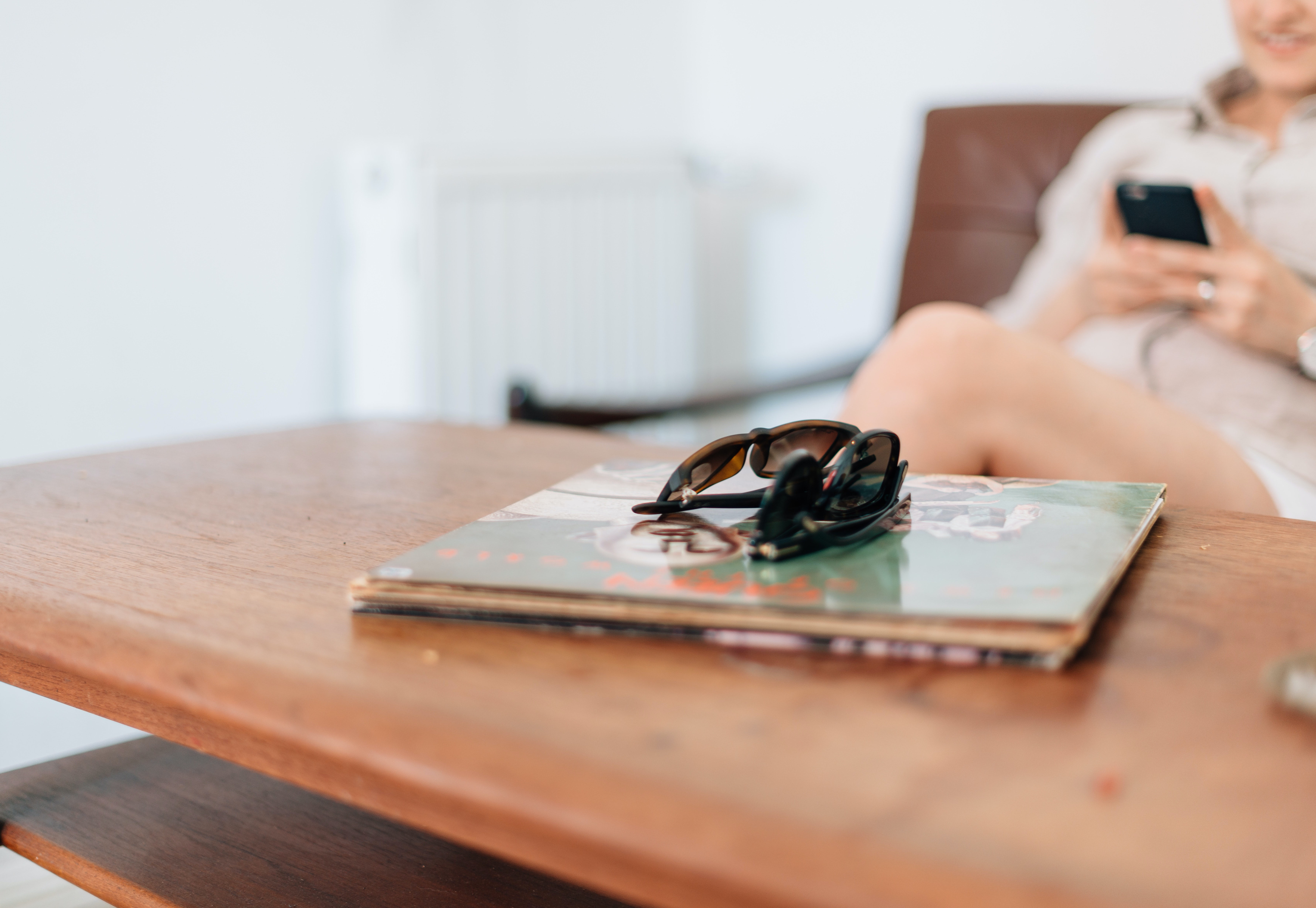 selective focus photo of two pairs of sunglasses placed on book
