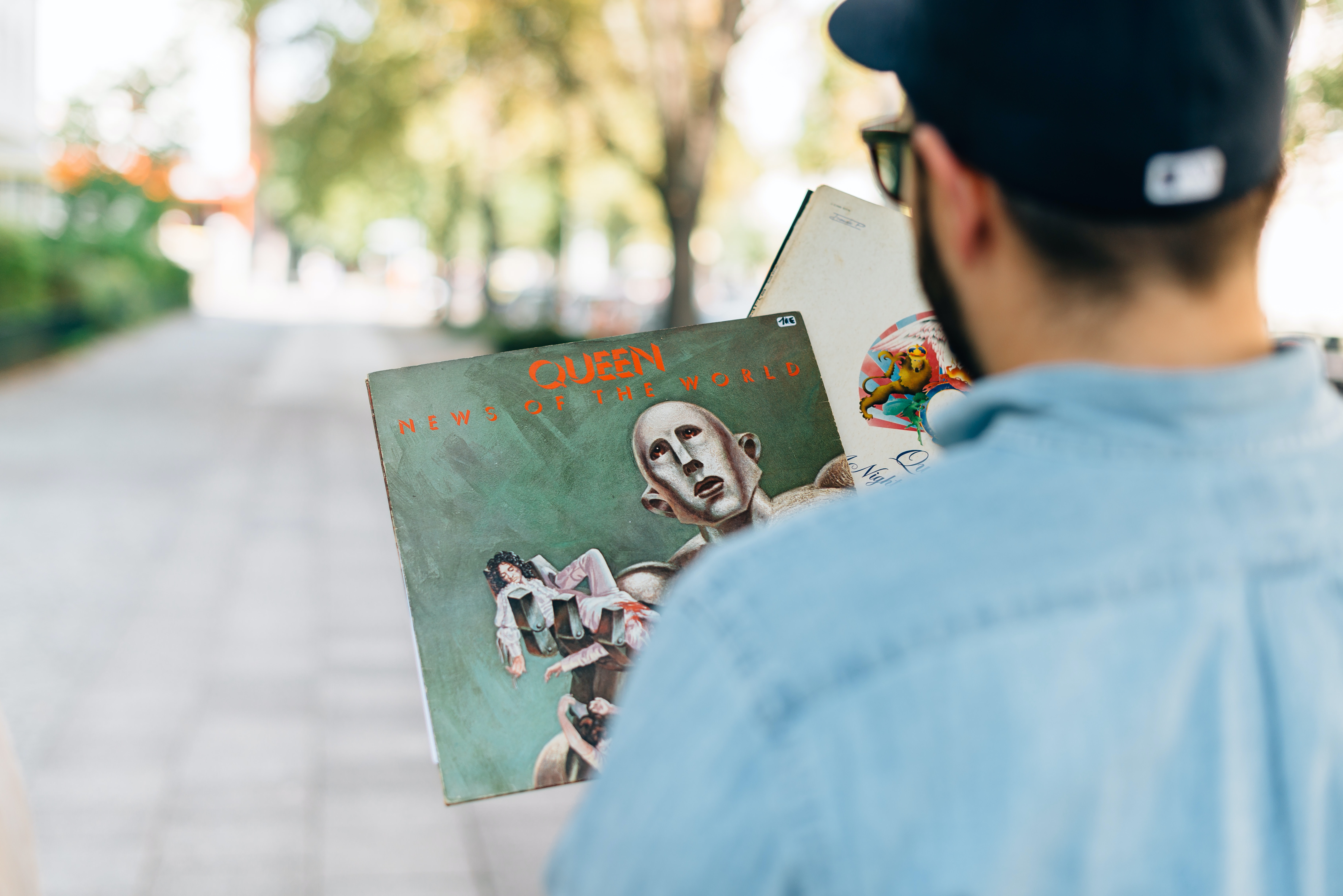 A view over the back of a man holding two Queen records