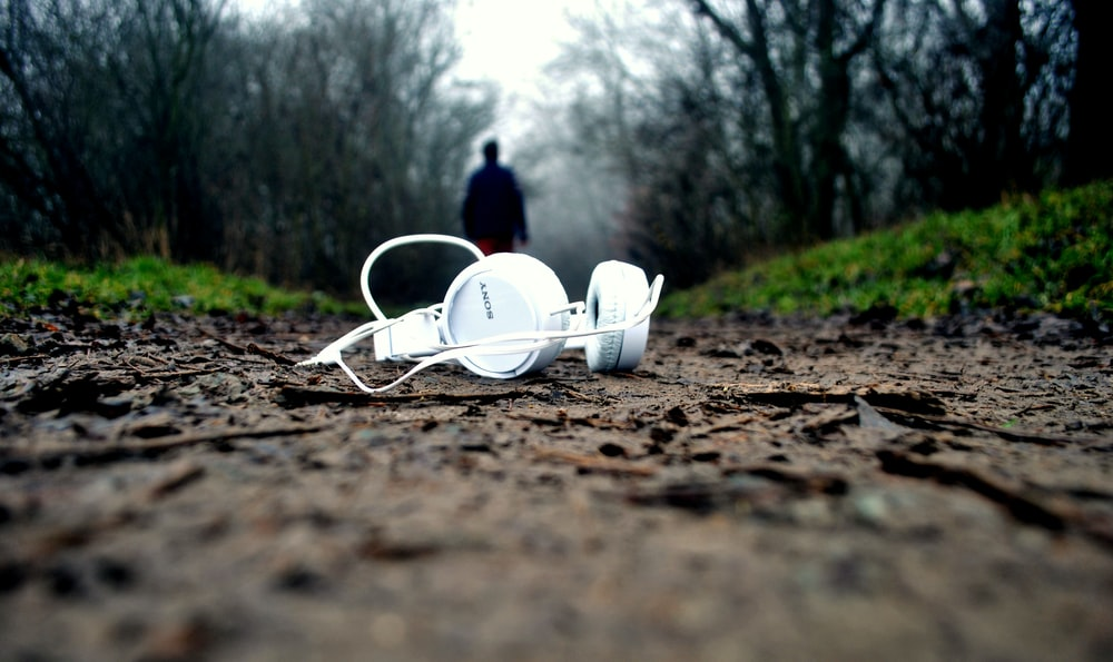 tilt shift lens photography of white corded headphones