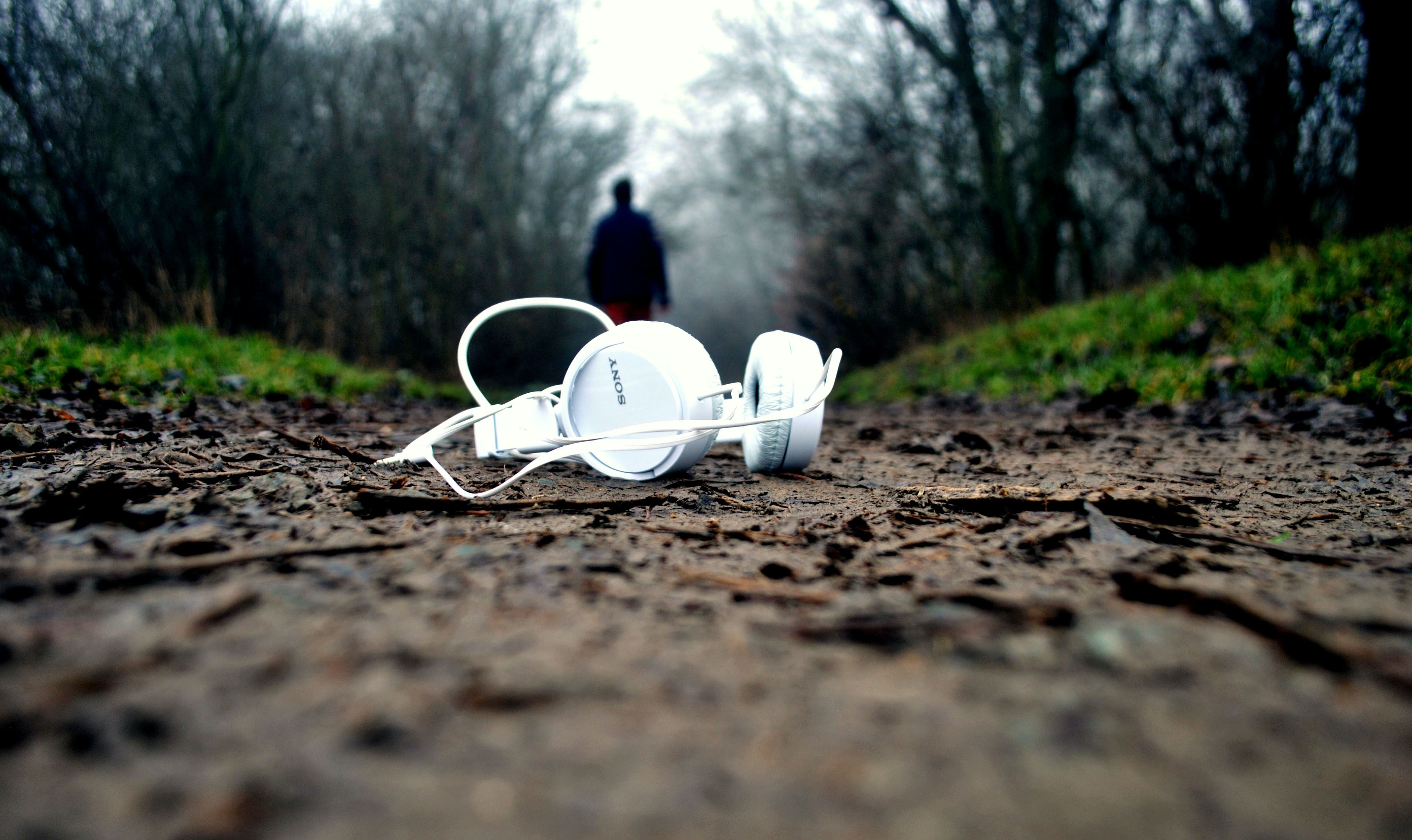 A white pair of headphones left behind on a dirt path
