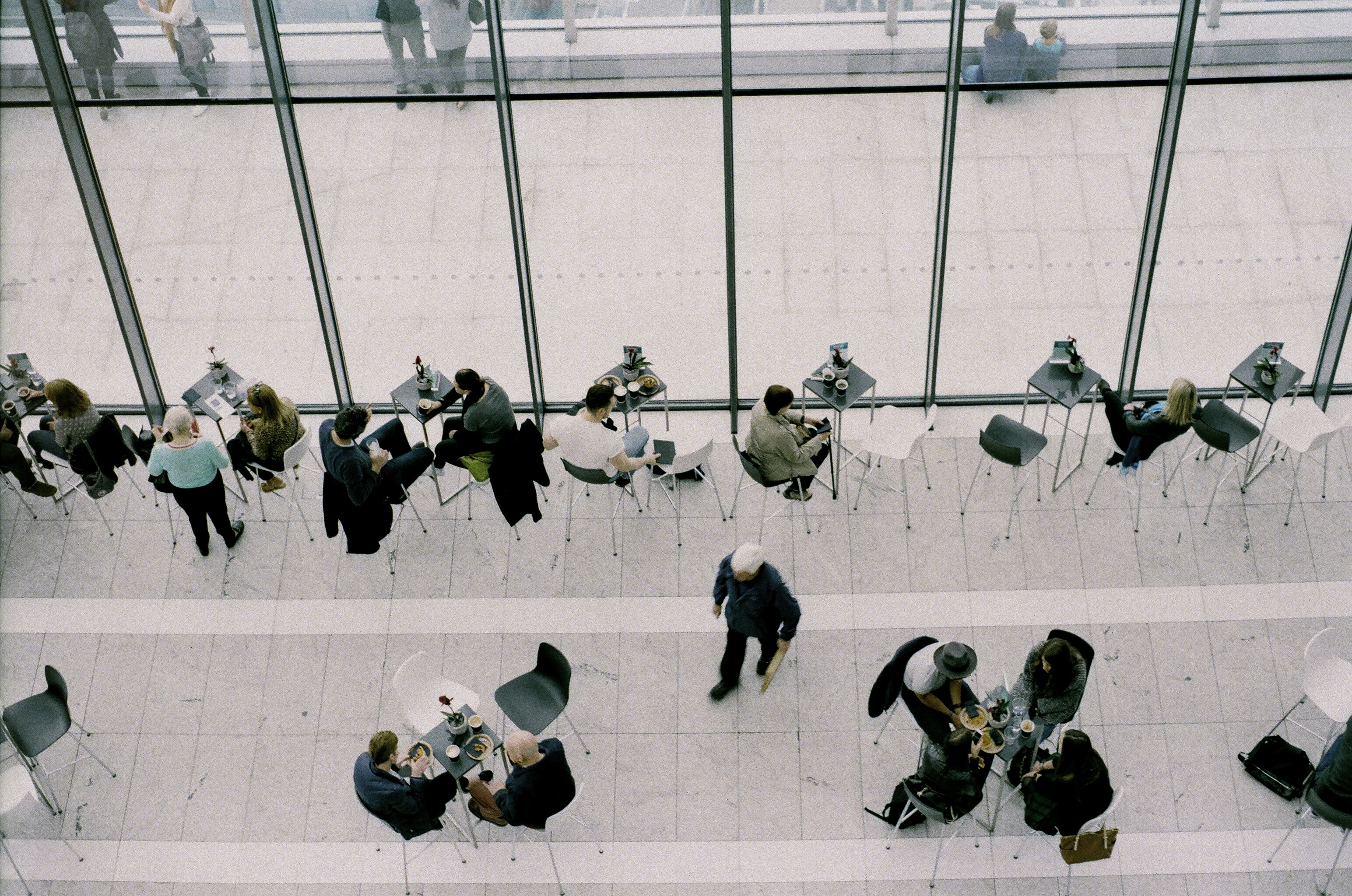 An overhead shot of people eating and talking at tables in a public space