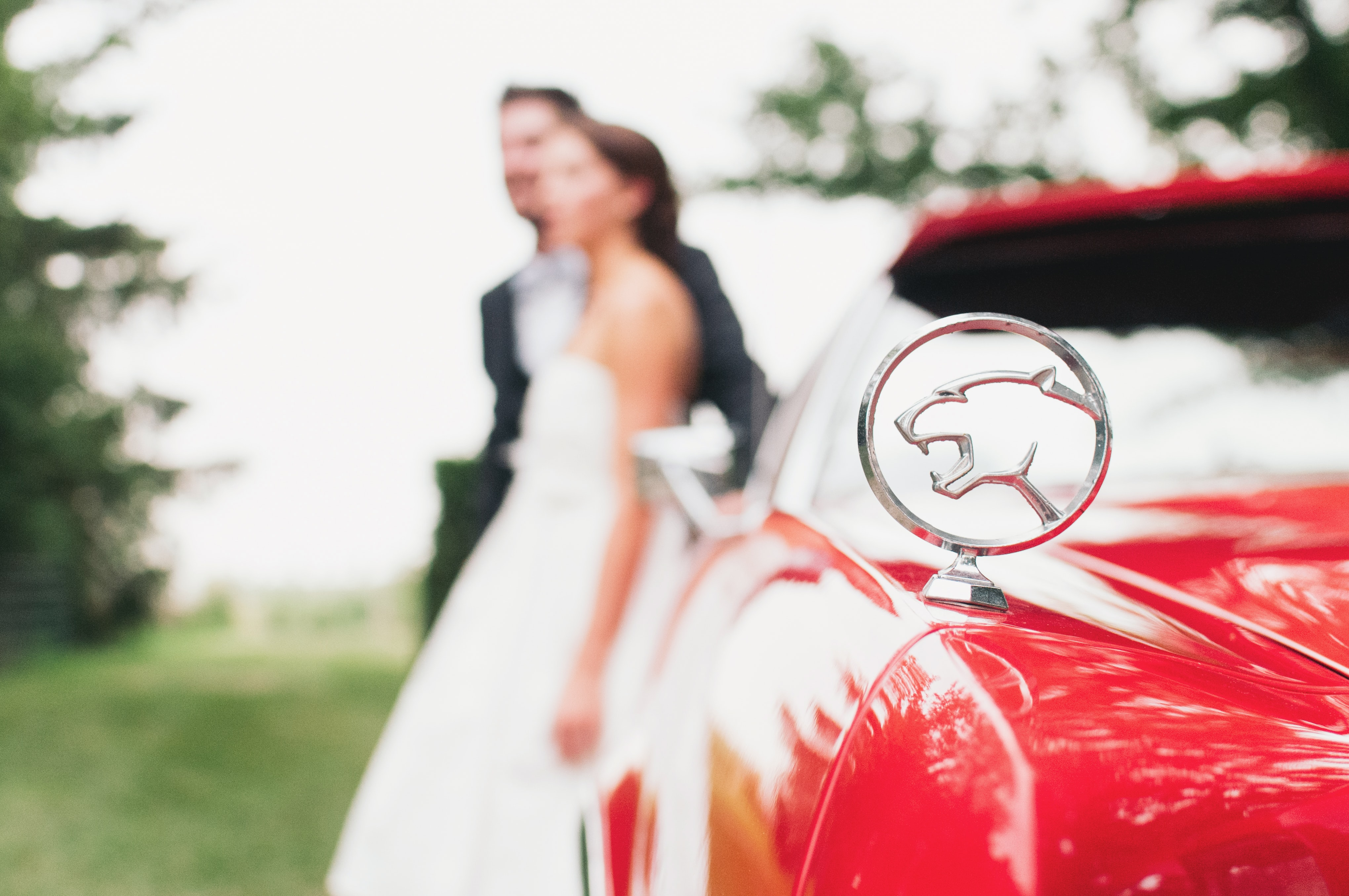 Vintage red jaguar car with married couple in background out of focus