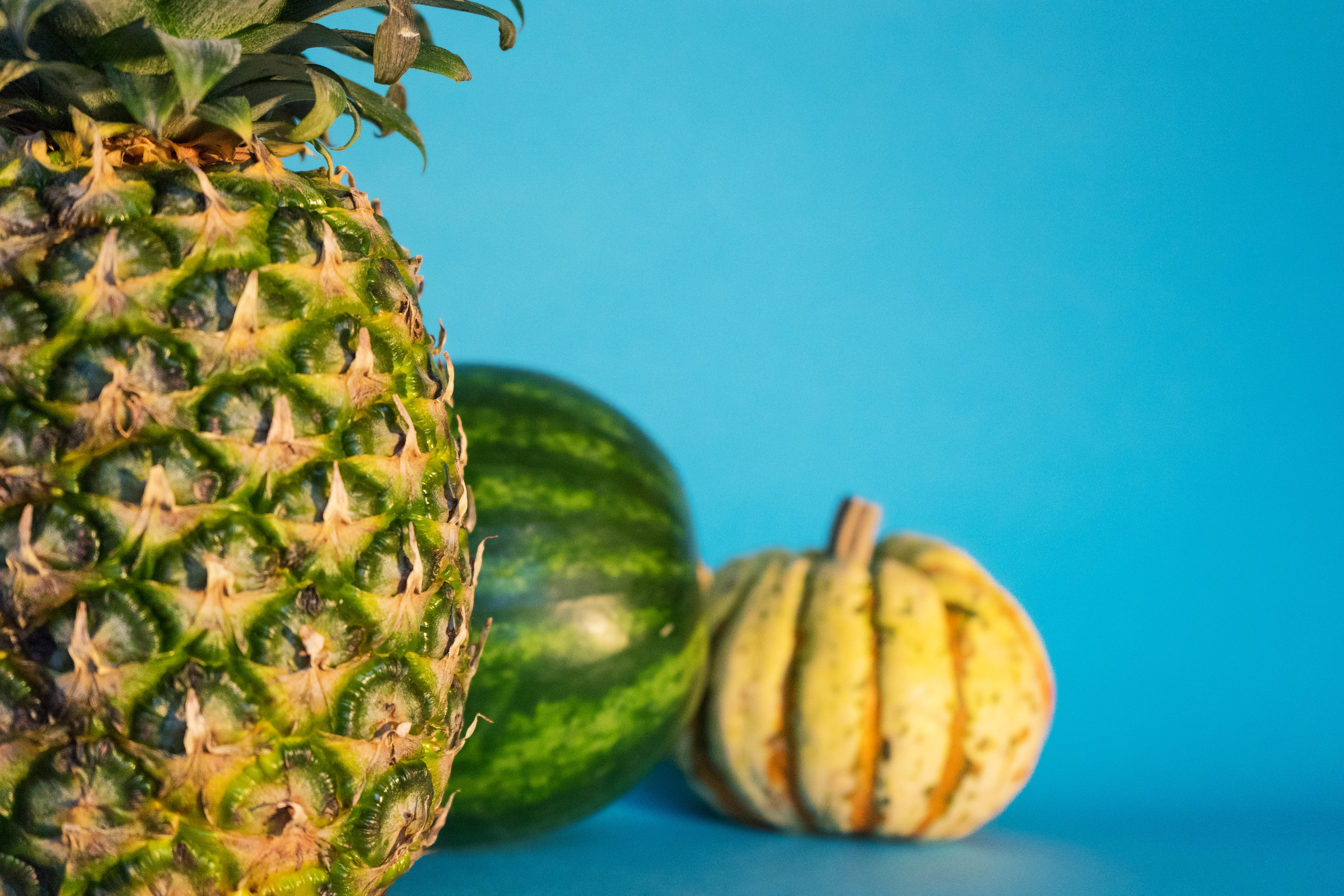 Pineapple, watermelon, and fall gourd on a blue background
