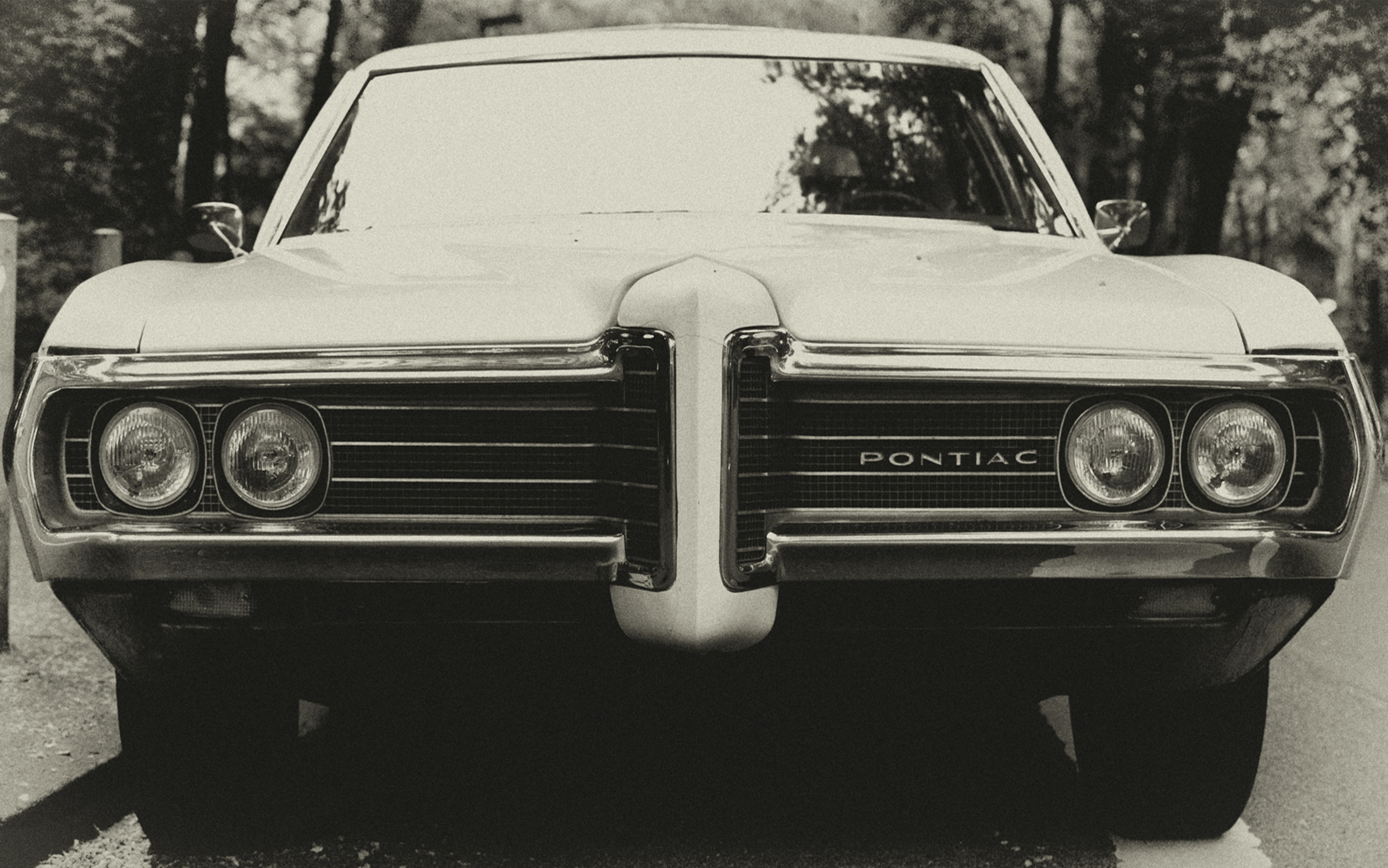 Front view of a vintage Pontiac in black and white.