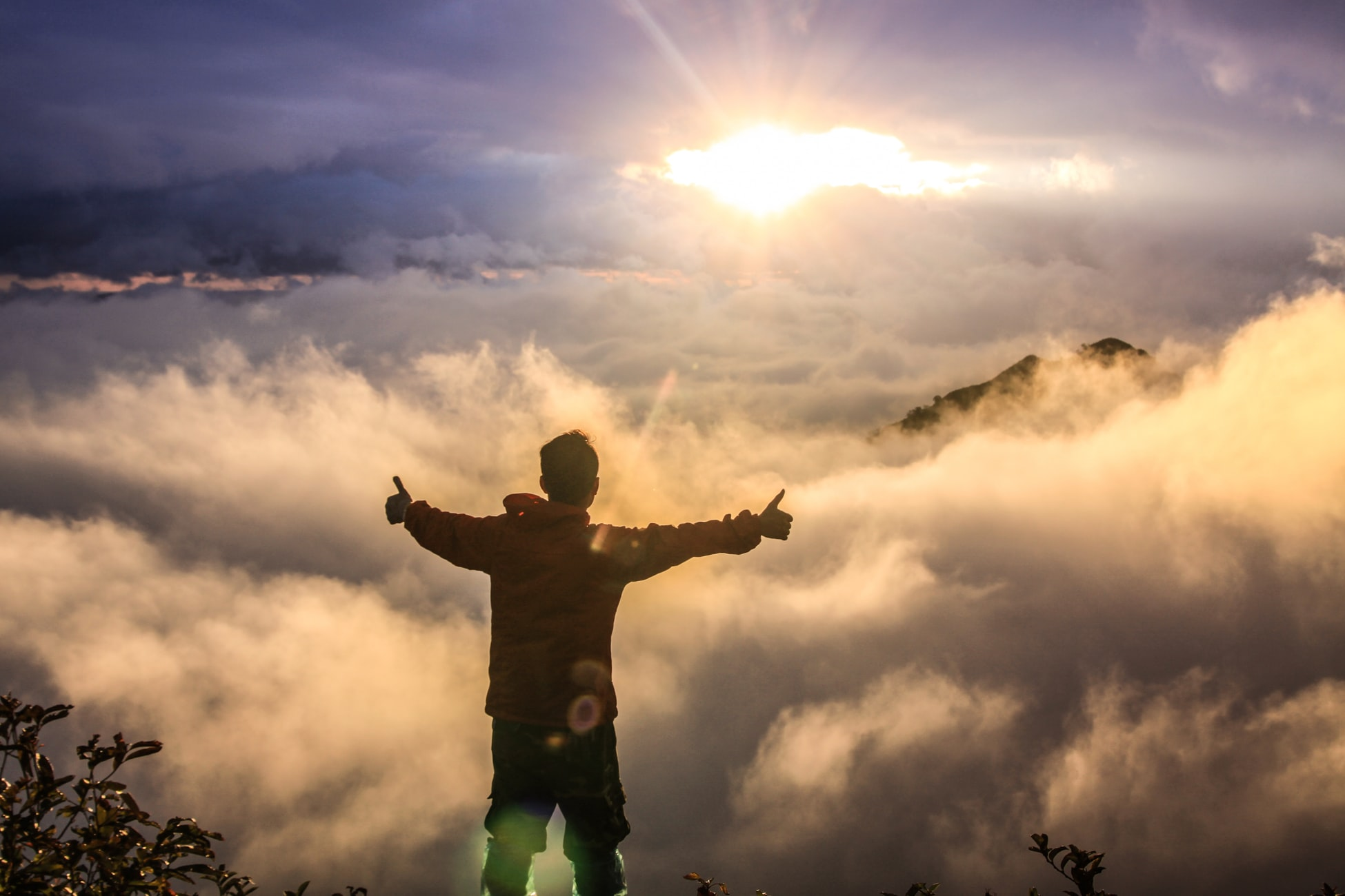 Man standing on a mountain giving two thumbs up