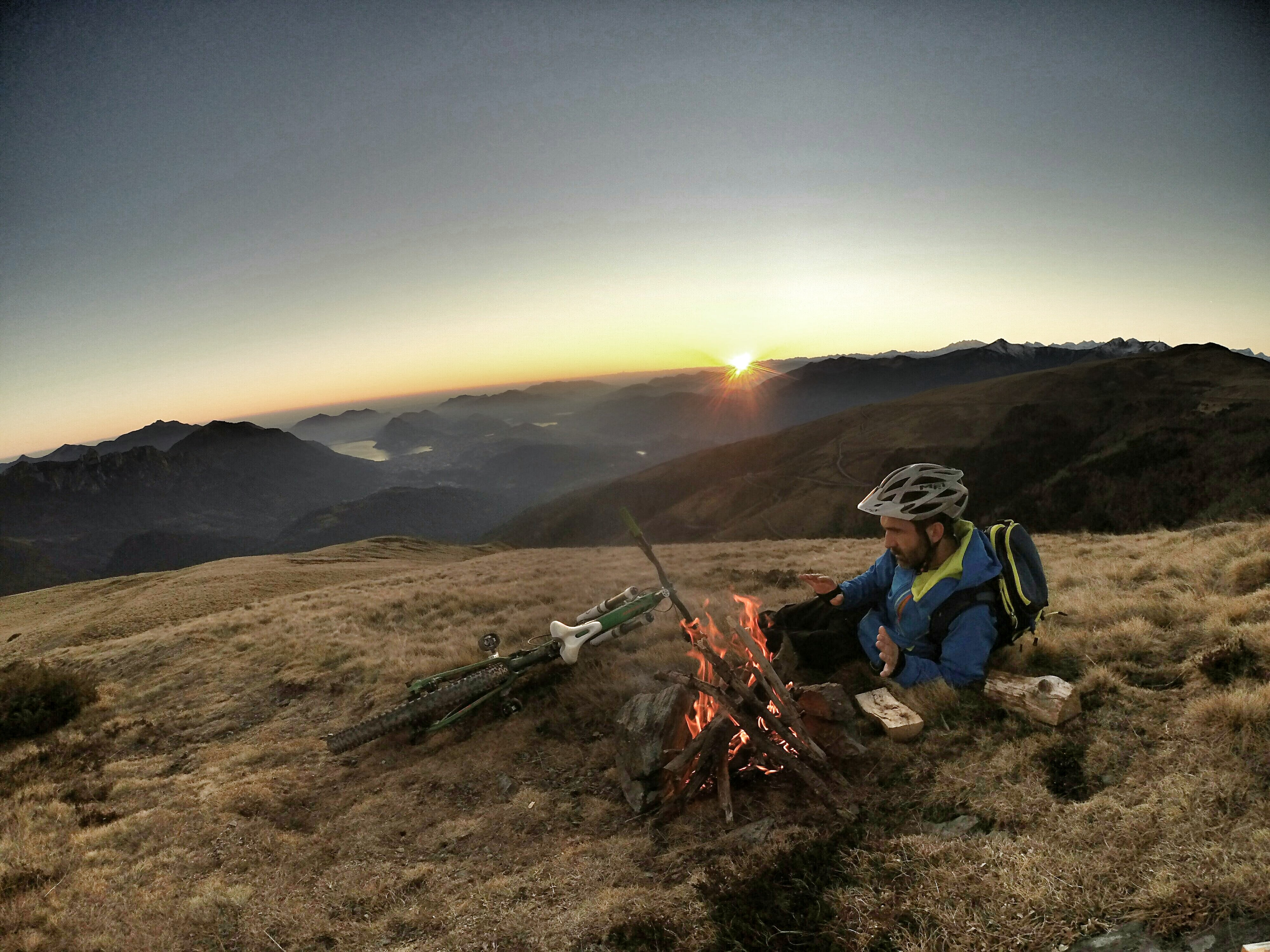 man laying on brown grass infront of bonefire during sunrise