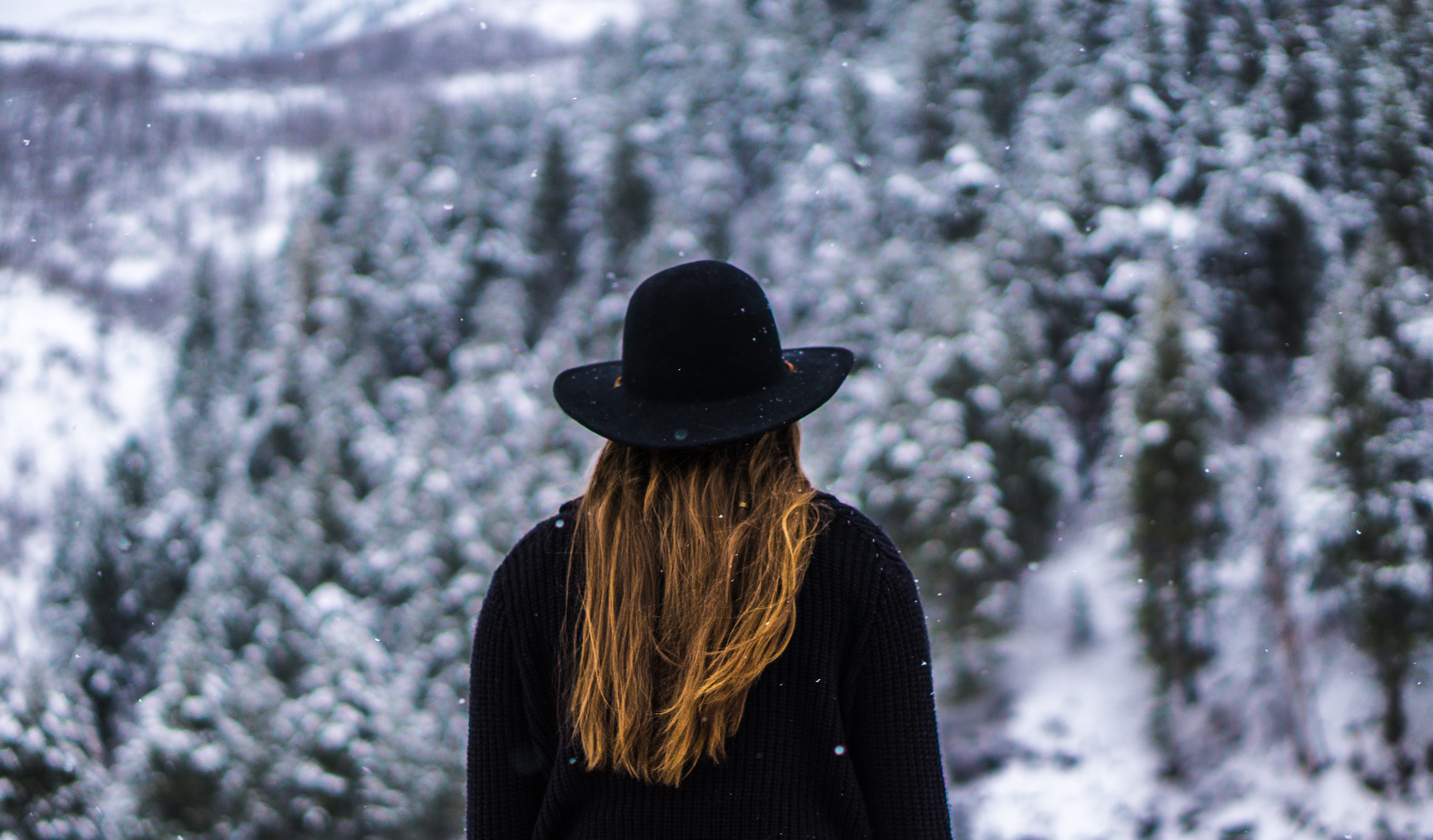 A person with long, red hair and a black coat and hat takes in the view of snow covered trees as snow falls