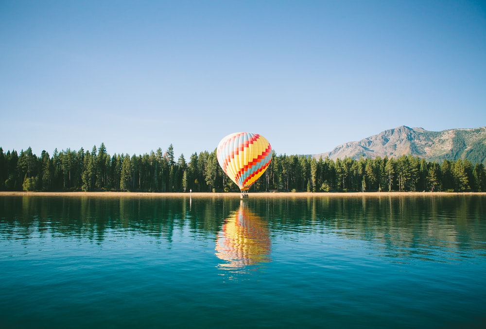 yellow, red, and blue hot air balloon near trees and body of water under blue sky during daytime