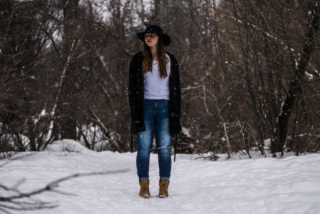 Женщина, стоя на вершине покрытой снегом земле, окруженные голыми деревьями