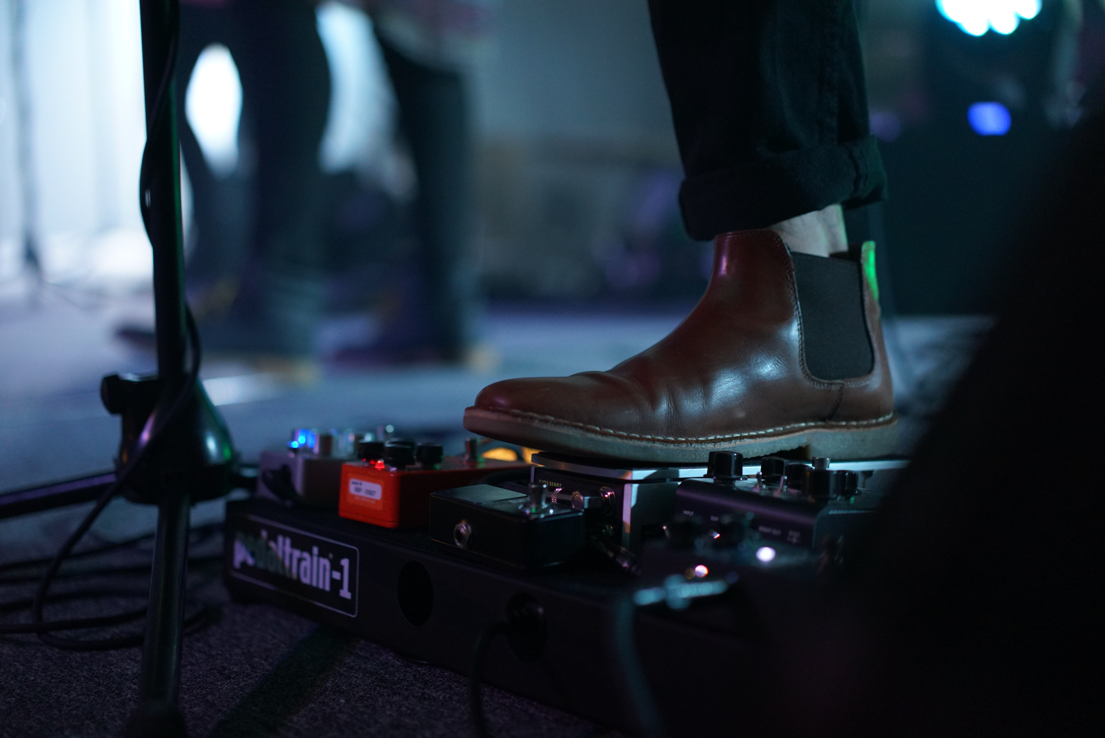 Musician's boot steps on guitar pedal near microphone stand