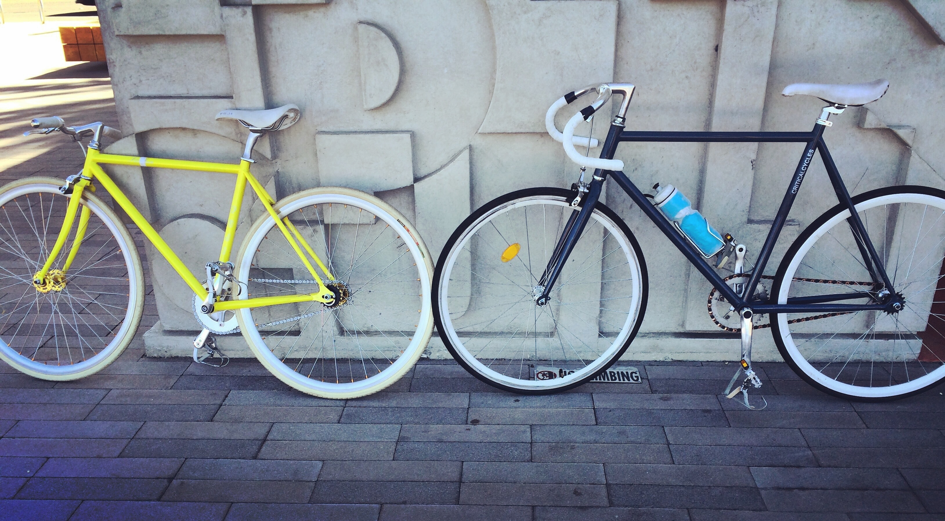 A yellow bike and a blue bike with a blue water bottle leaning against a wall in San Diego