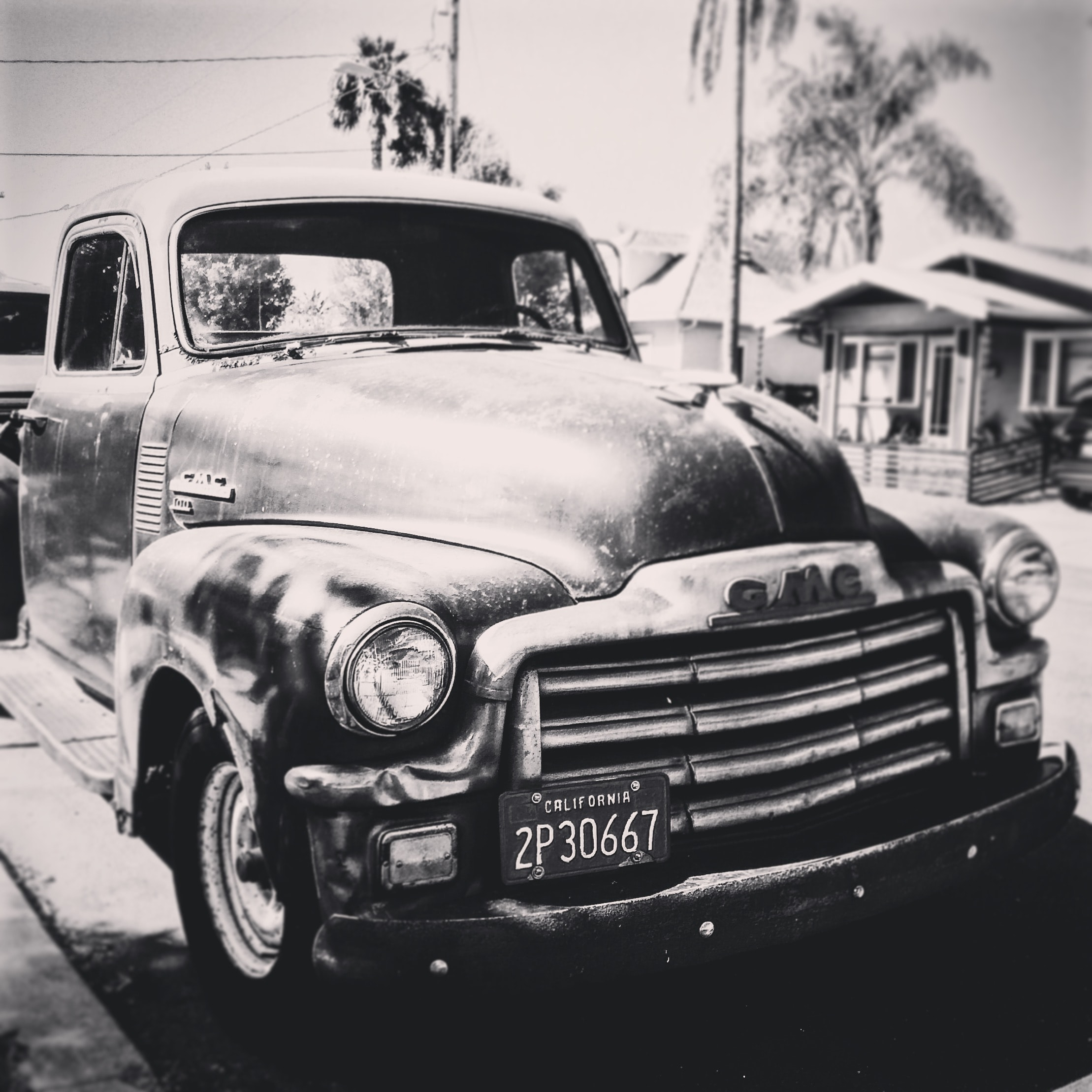 Black and white photo of vintage truck parked in a beach setting.
