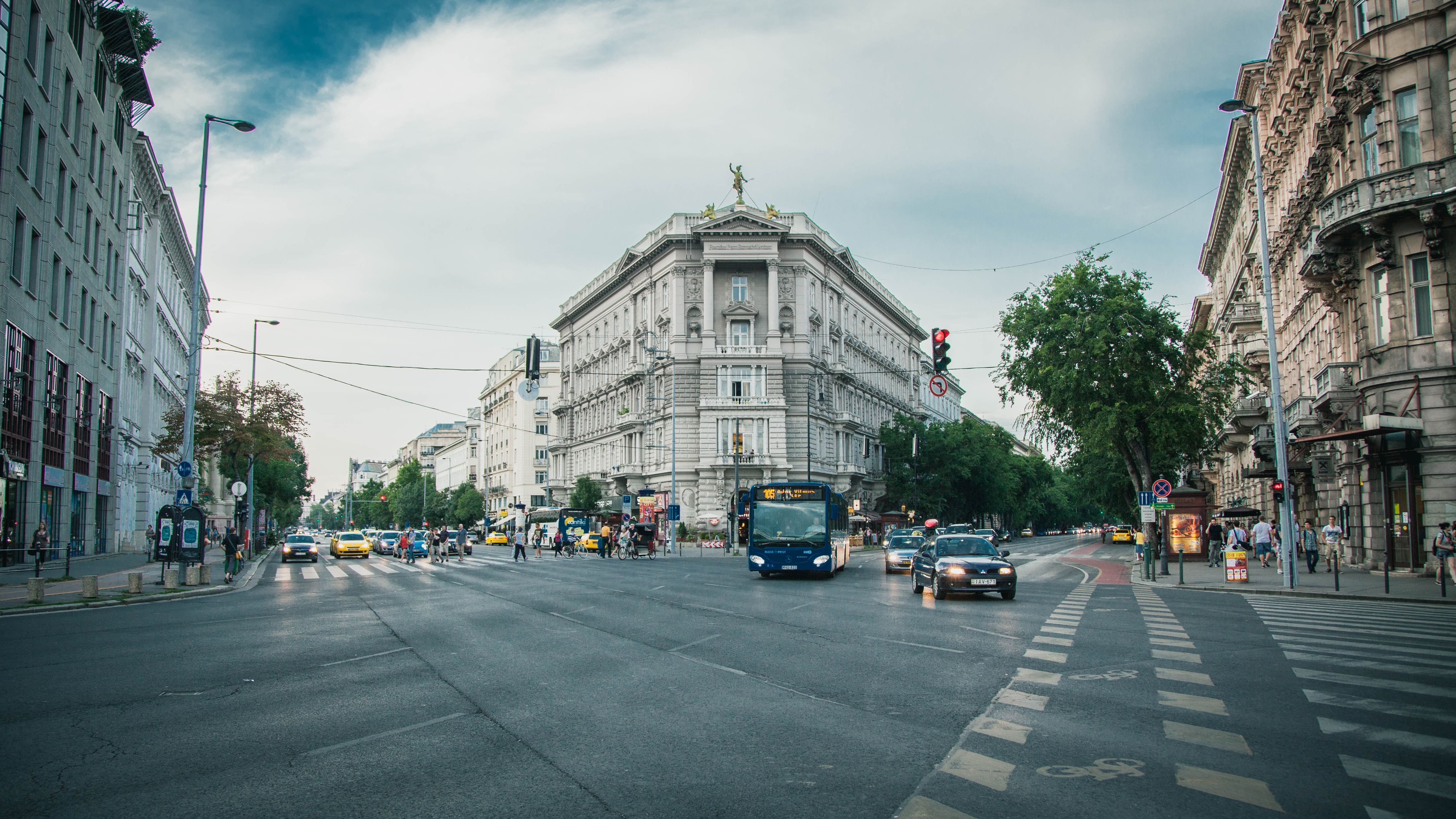 Busy crossroads at daytime with traffic and traditional architecture in Budapest