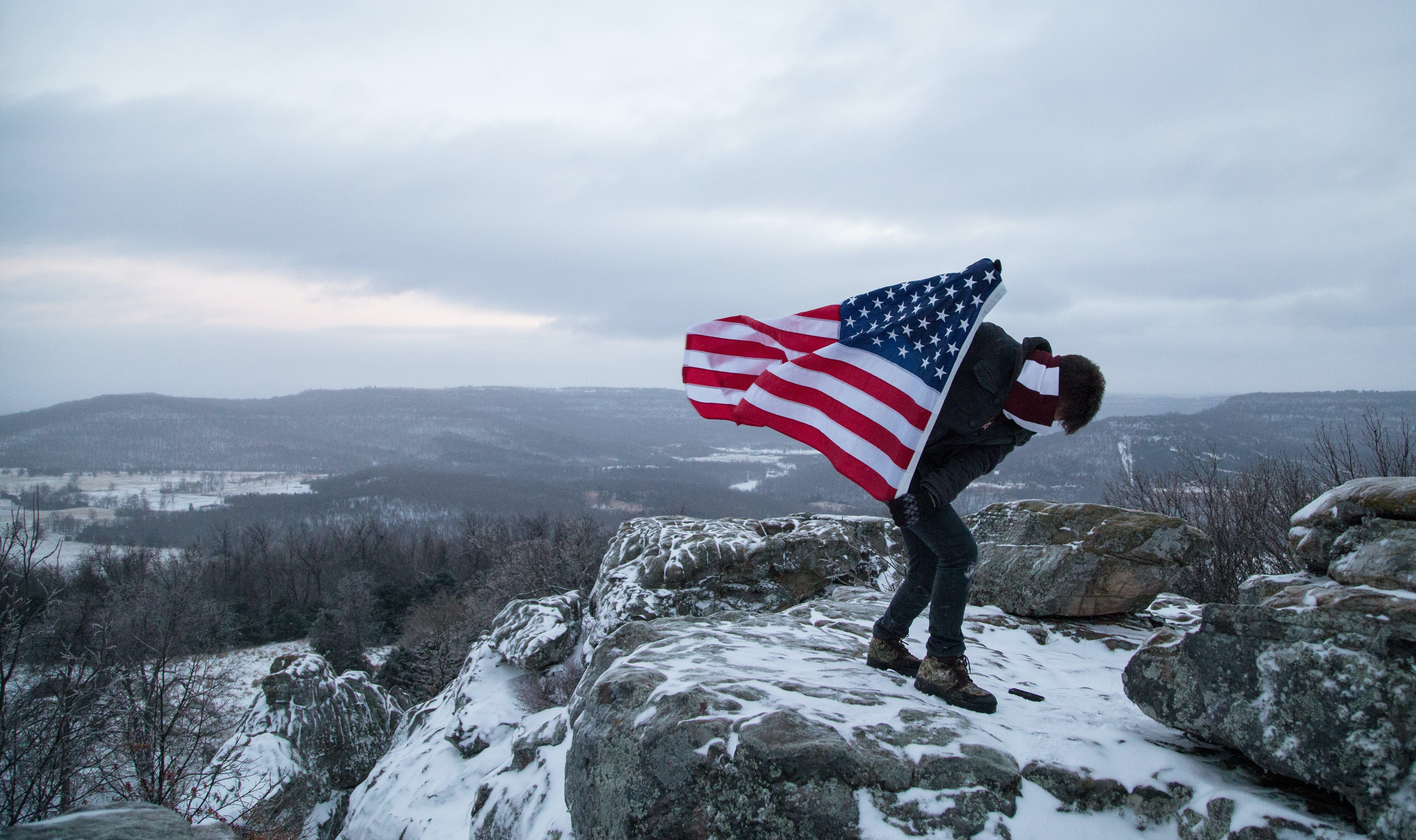 A climber holds the American flag while standing on the peak of a snowy mountain