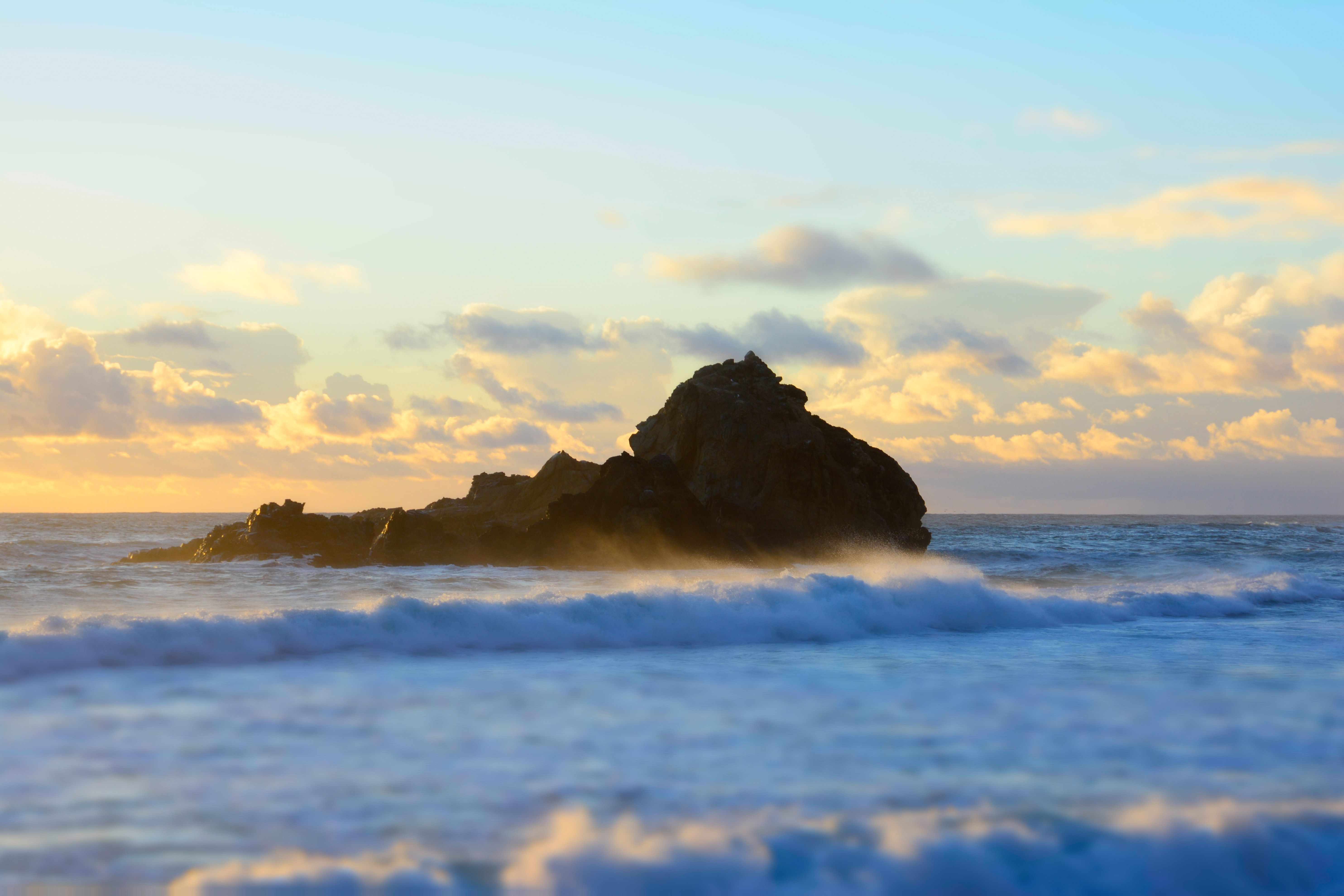 Waves around the ocean rock during sunset at Pfeiffer Beach