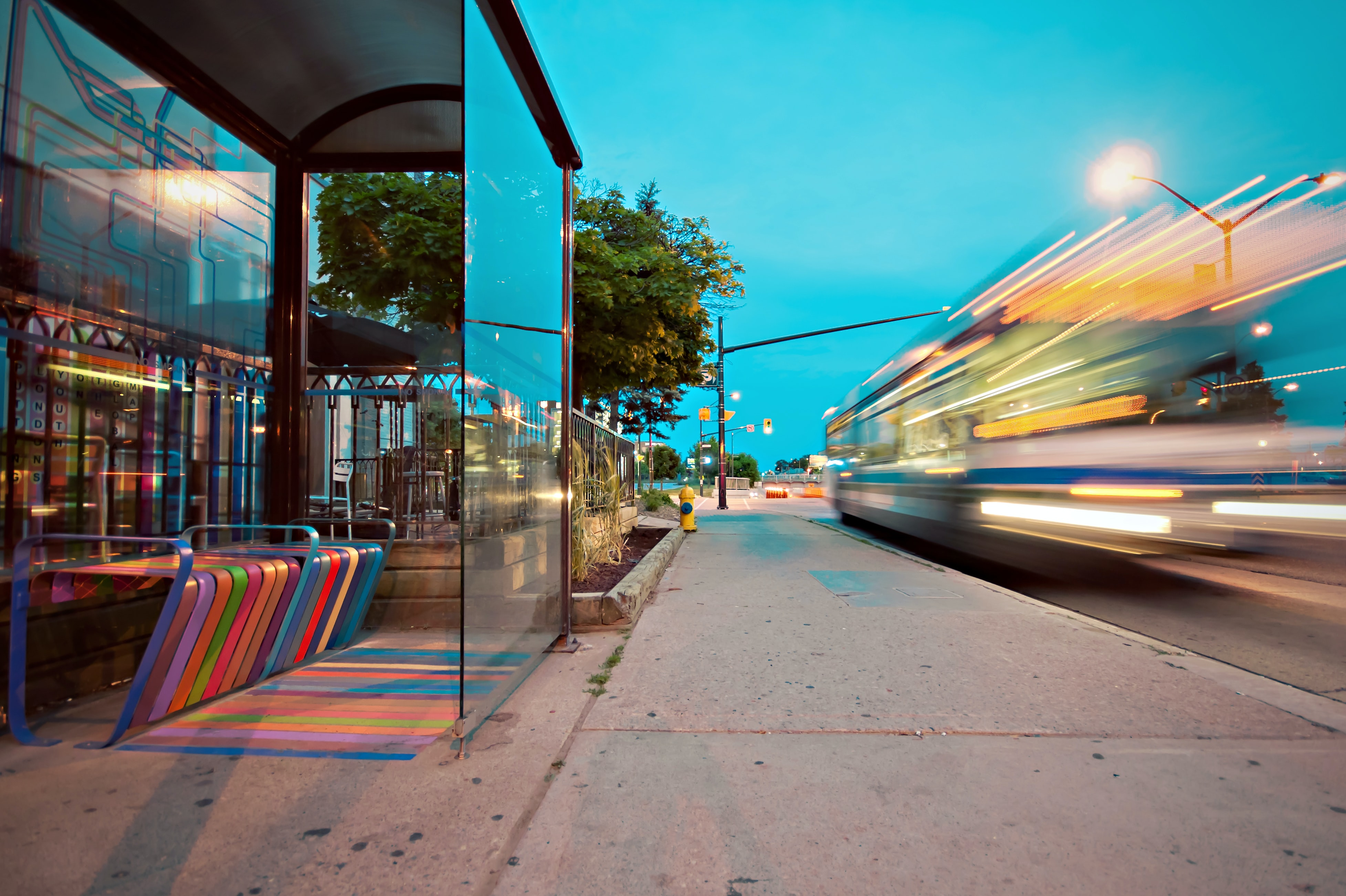 A long-exposure shot of a bus driving past a glass wall