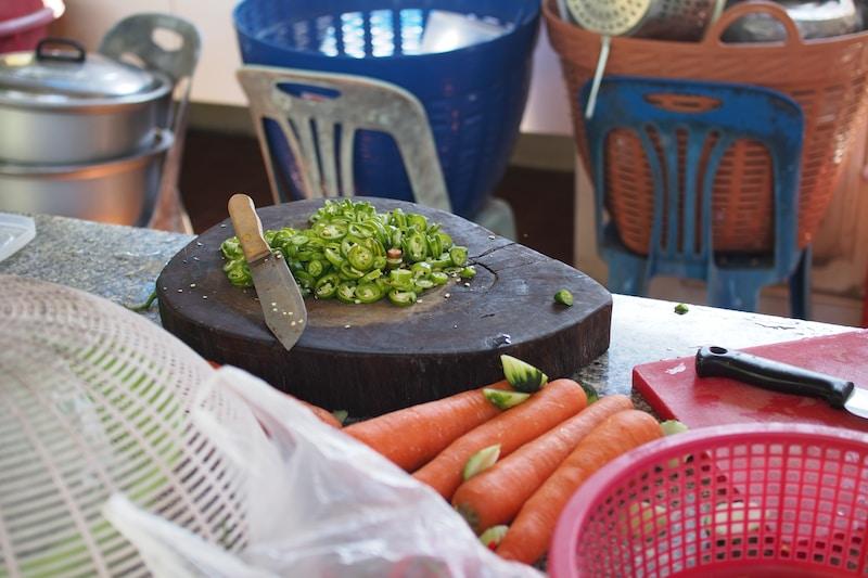 green vegetable near beige kitchen knife both on brown wooden cutting board