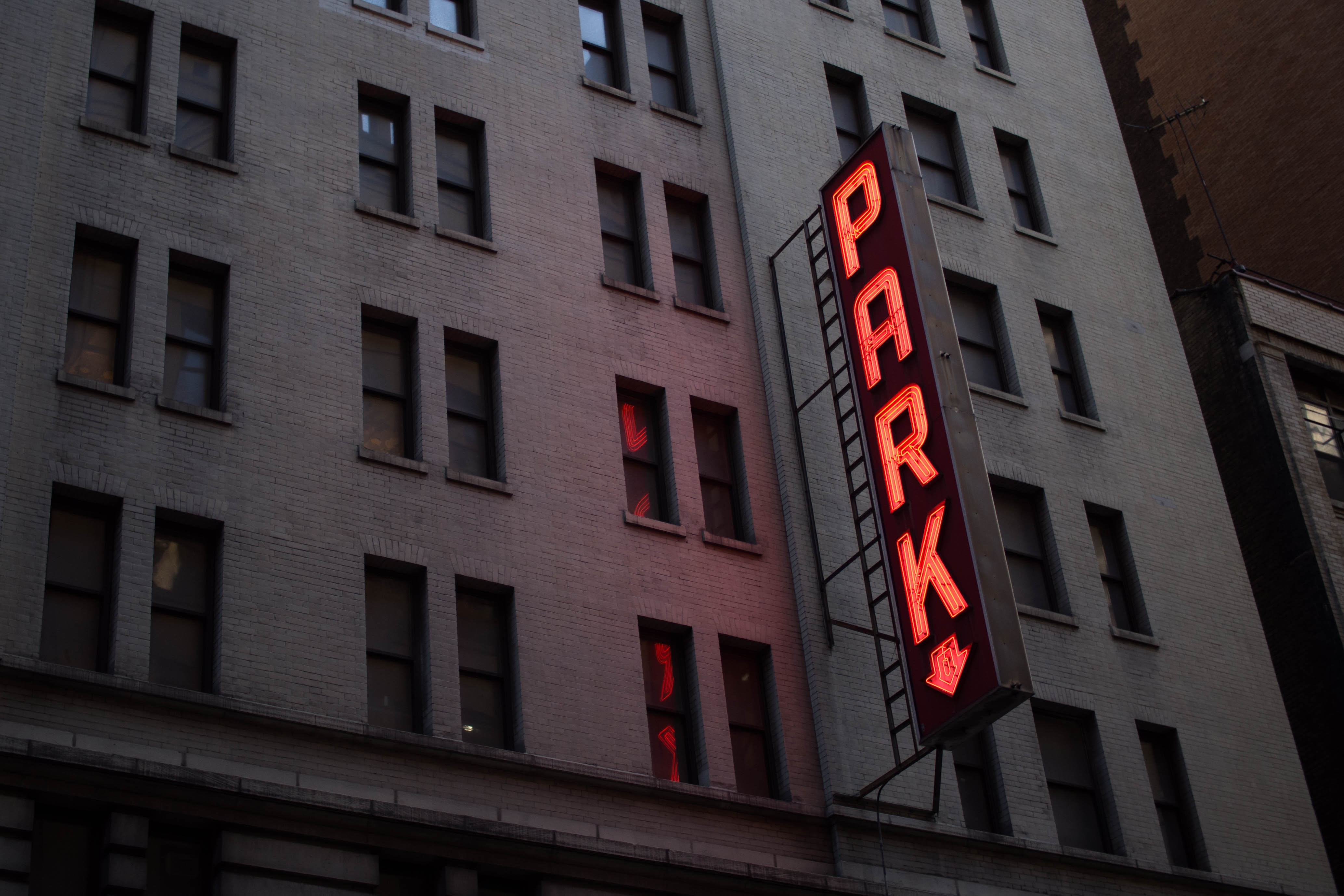 """Neon sign reads """"PARK"""" on a dark building in New York"""