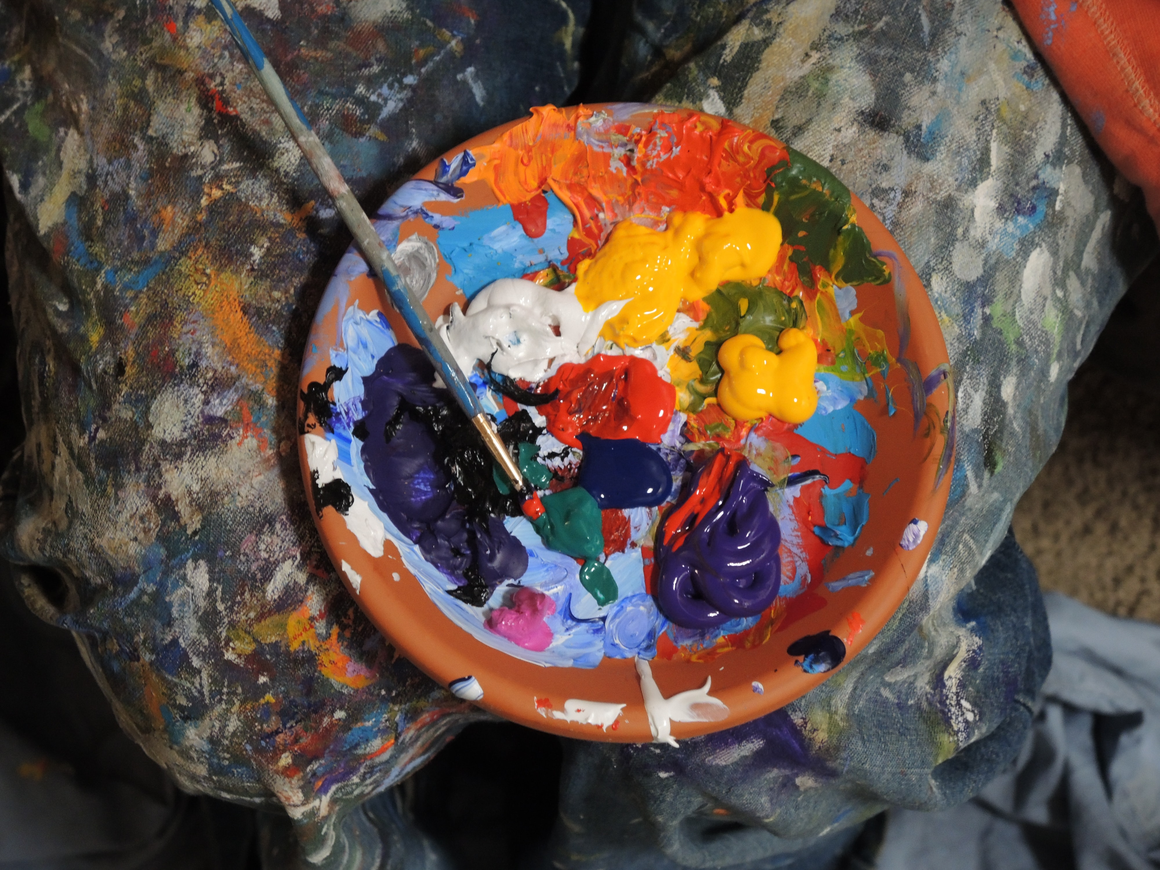 Mix of paints in a orange bowl with paintbrush sit on a messy background
