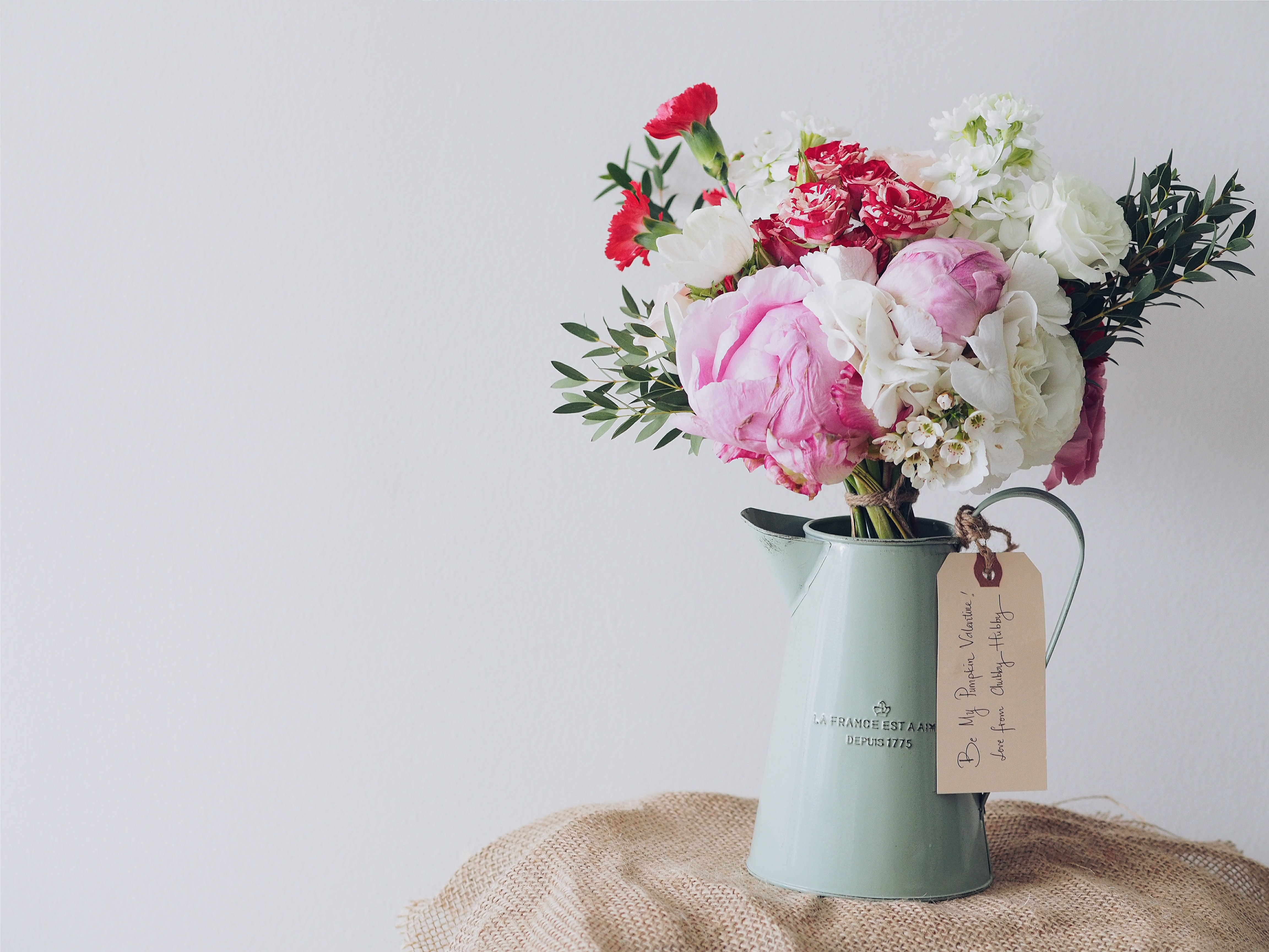 Valentine's Day floral arrangement of roses, carnations, and peonies in a vintage pitcher