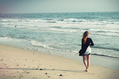 Woman walking on a sand beach