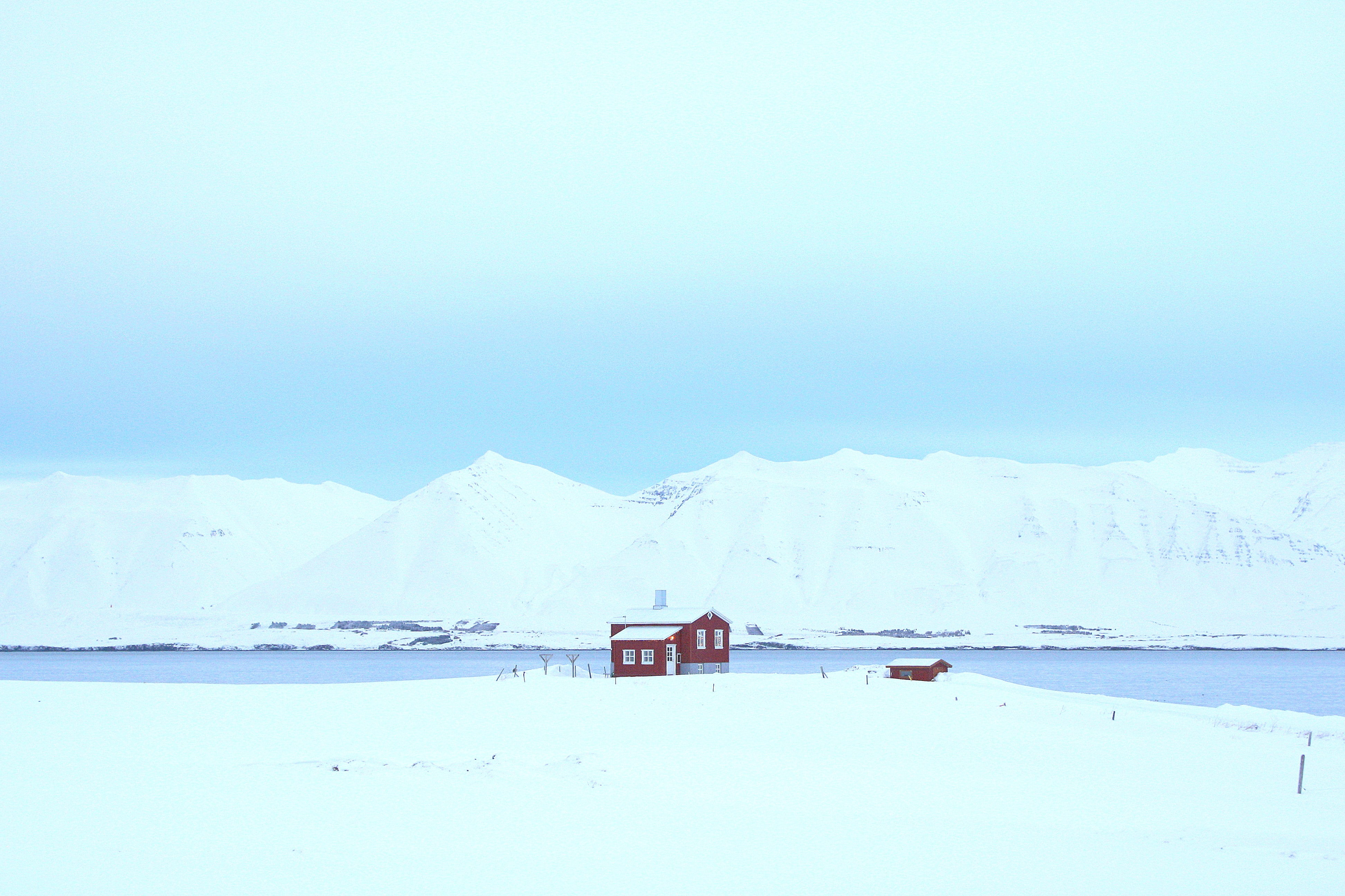 A lone cabin by the lake surrounded by white snow