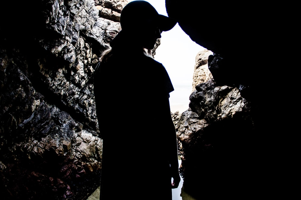 silhouette of woman standing inside cave