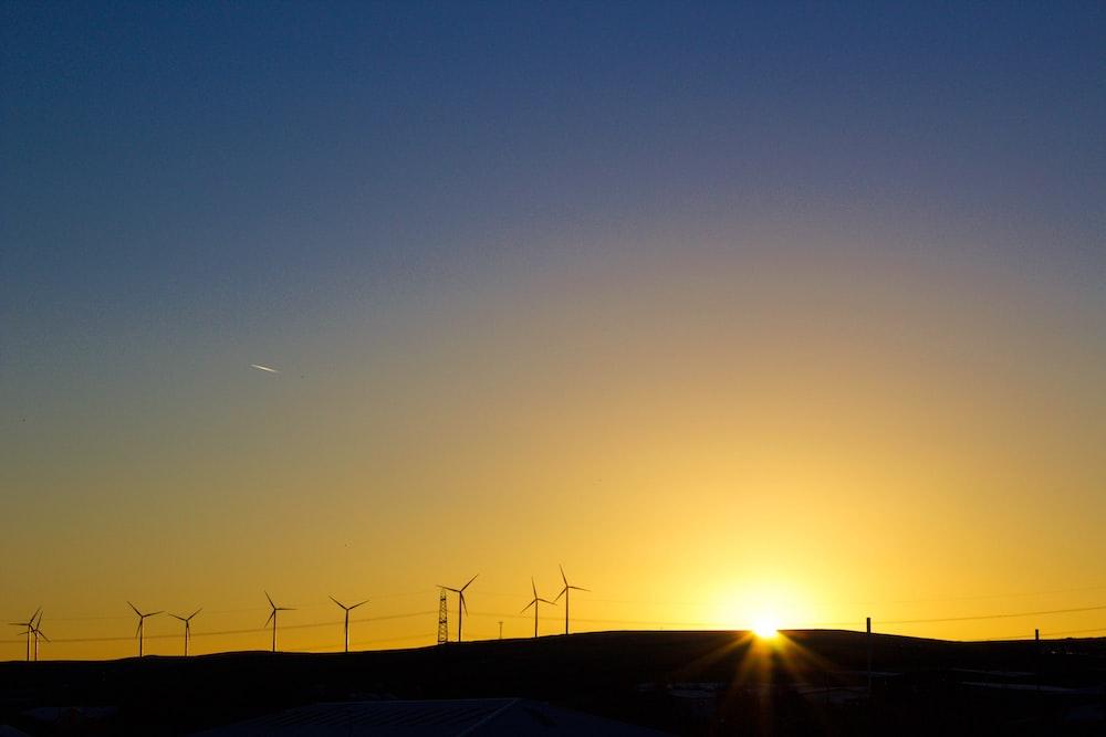 silhouette of road near windmills