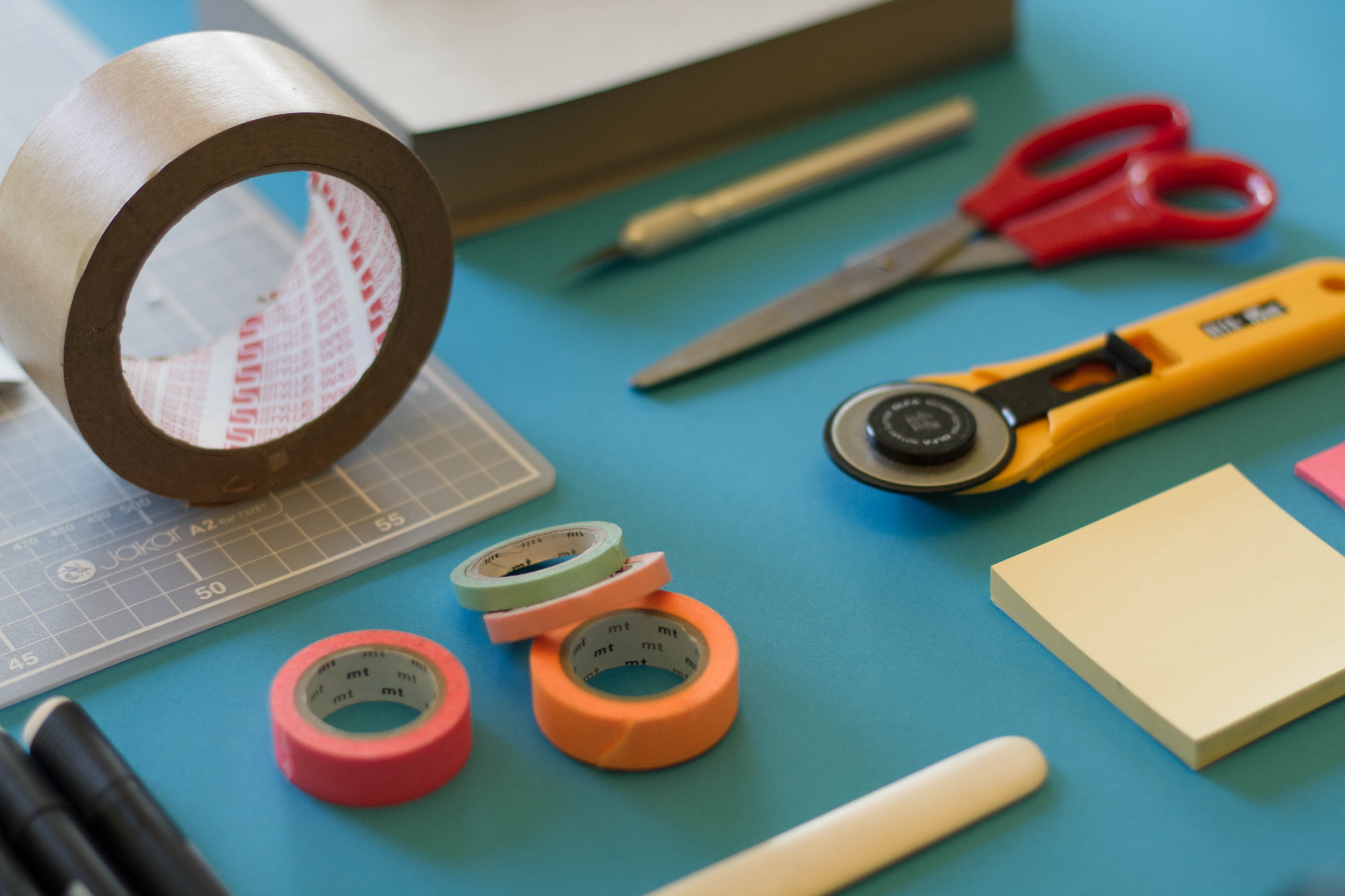 Colorful rolls of scotch tape, scissors and sticky notes on a table