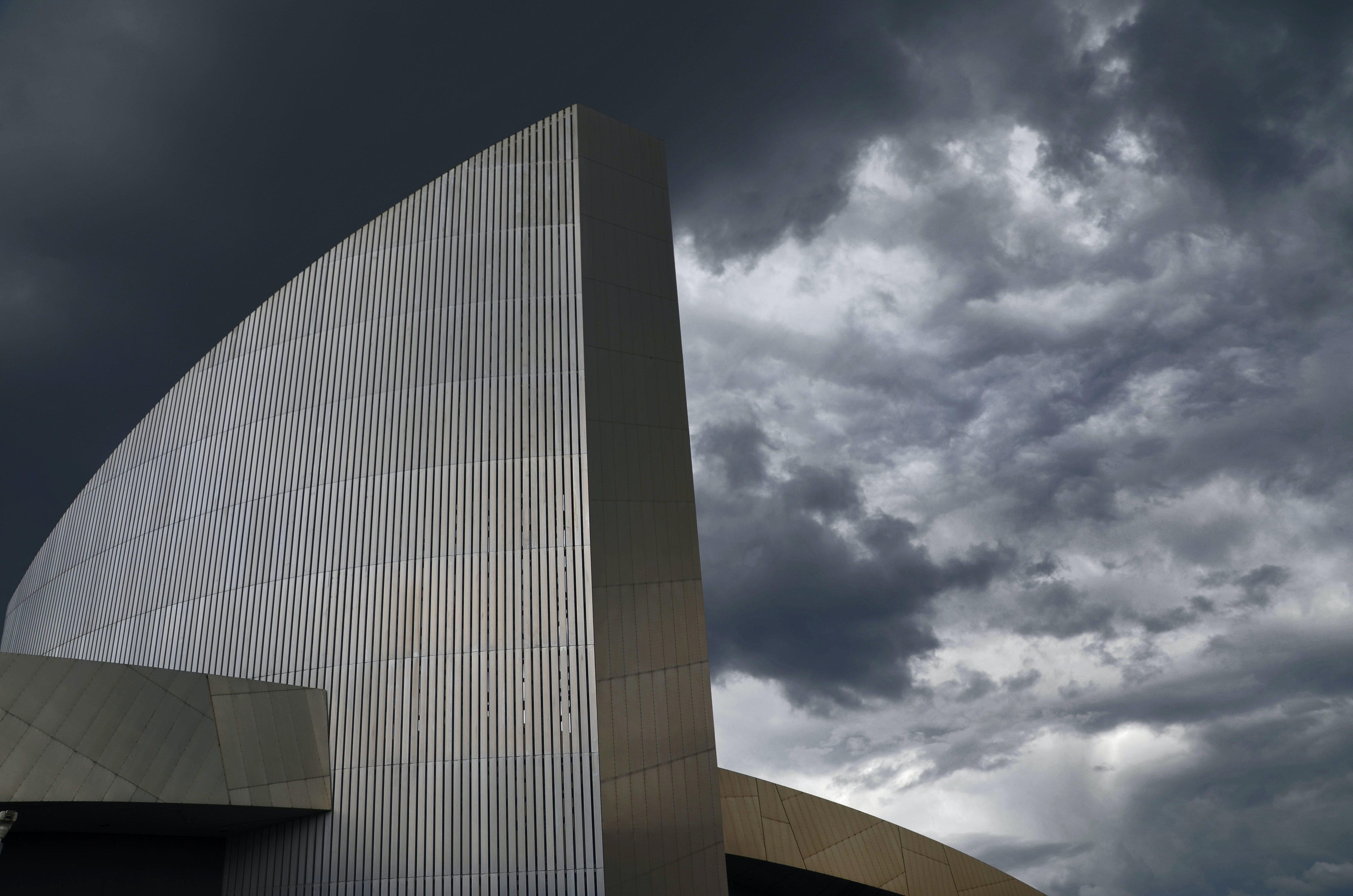 A postmodern building with cloudy skies in the background.