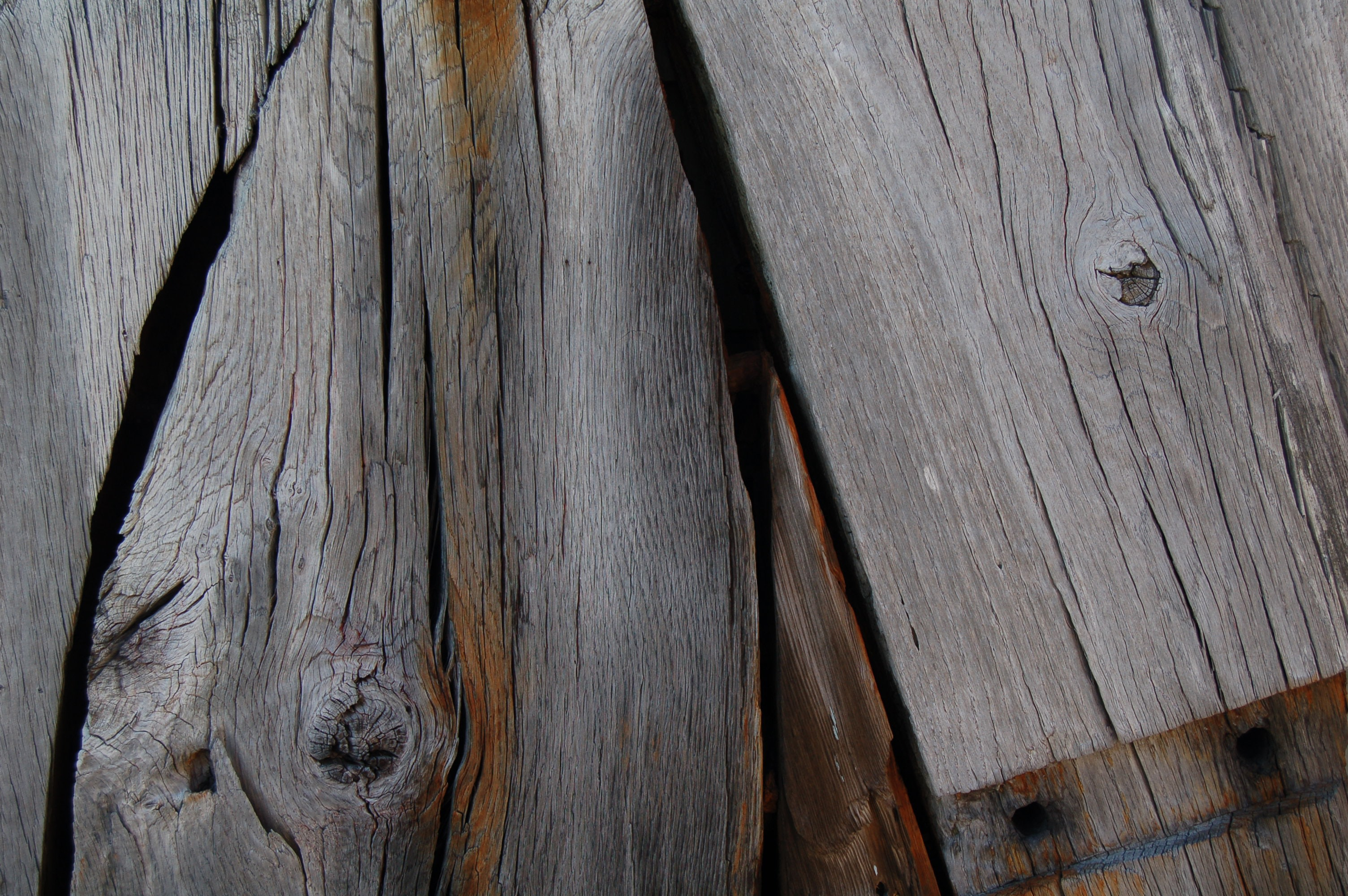 A close-up of weathered wooden planks with visible knots