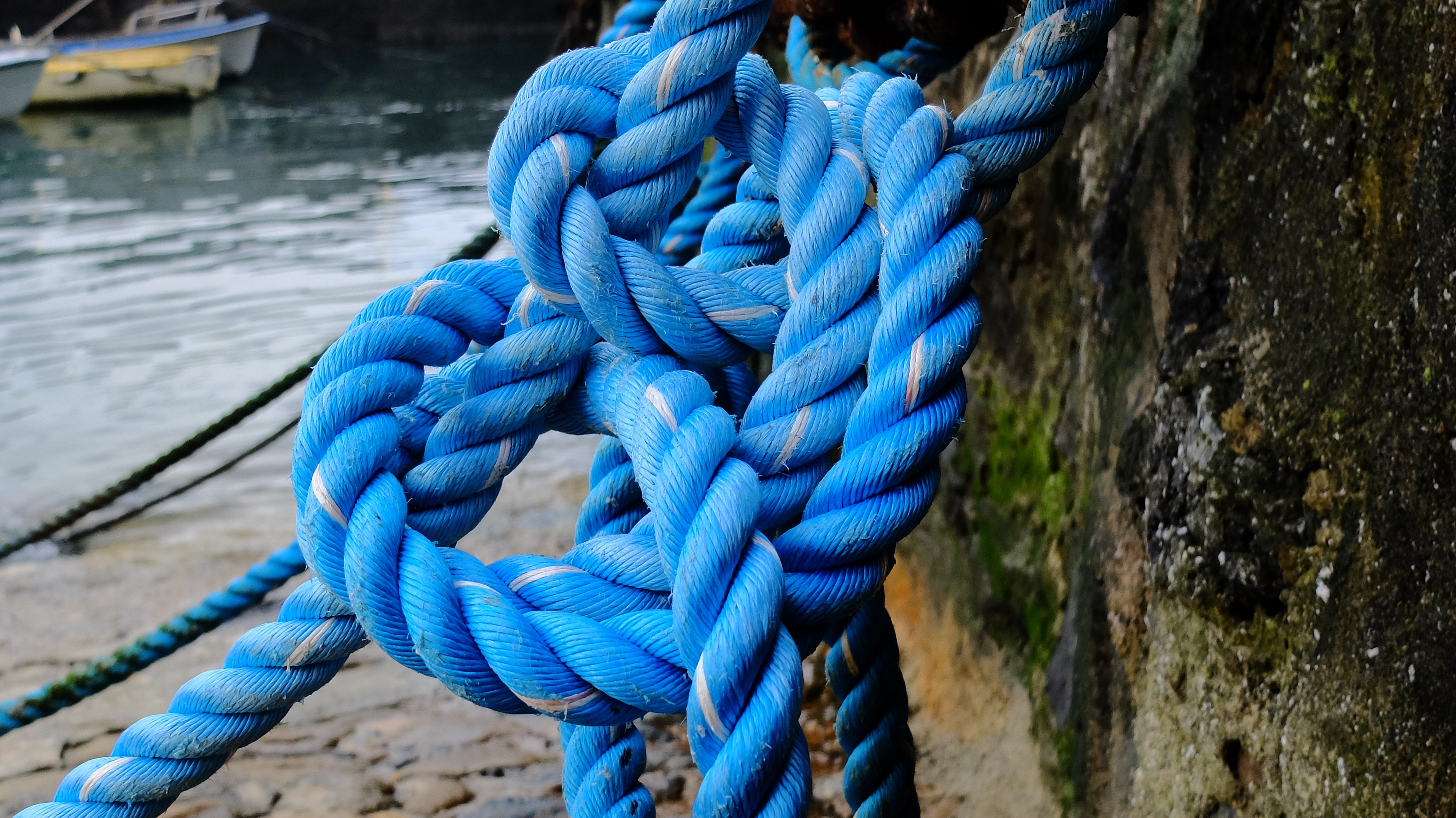 Thick blue boat rope tied in a knot at the beach in Mundaka