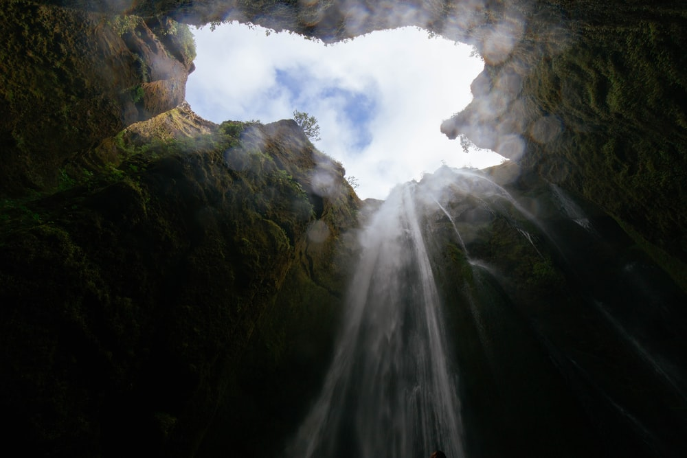 worm's eye view photo of cave waterfalls