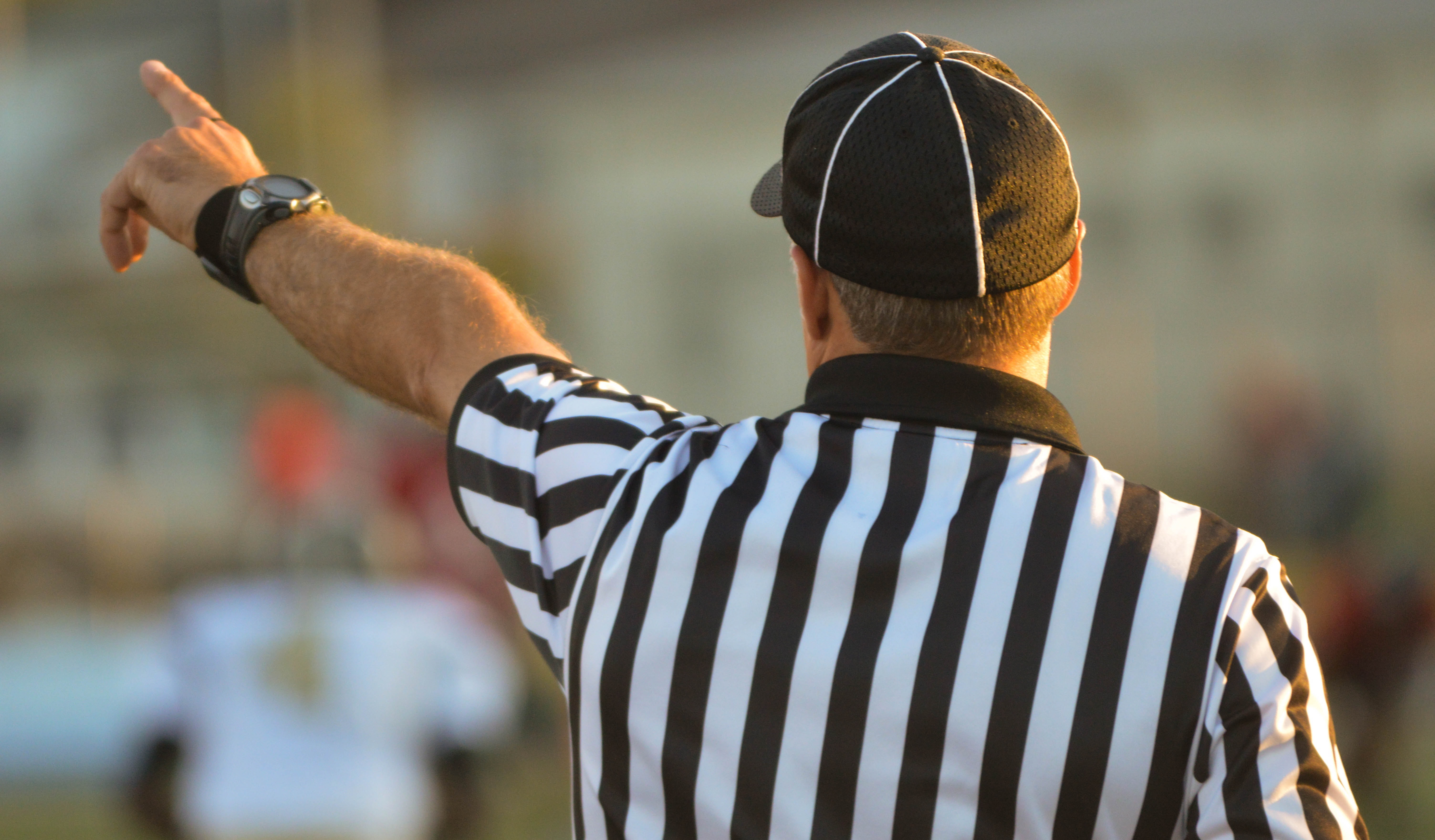 The macro view of a referee blowing a fowl in a baseball game