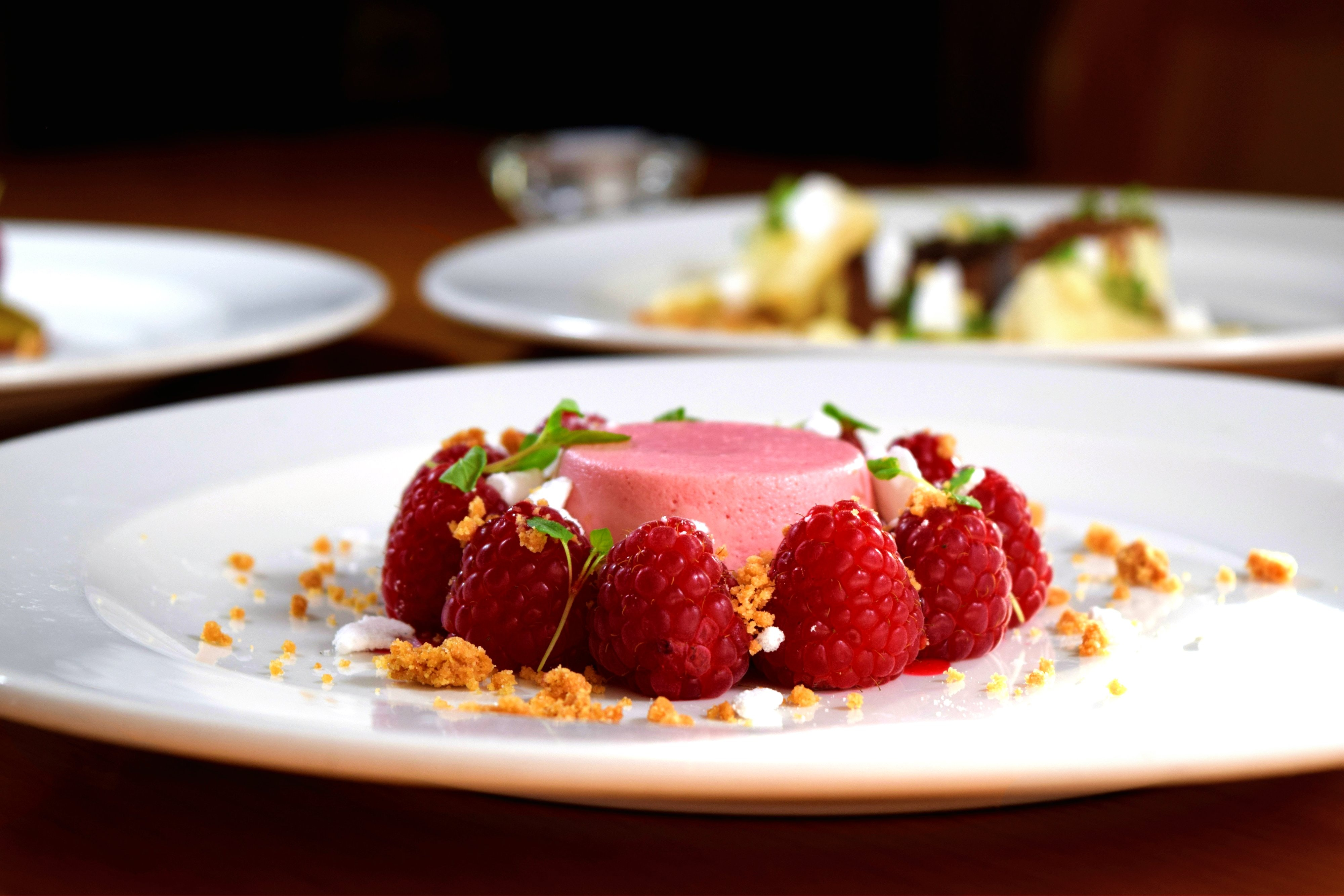 Small red desert surrounded by raspberries on a white plate with other desserts in the background
