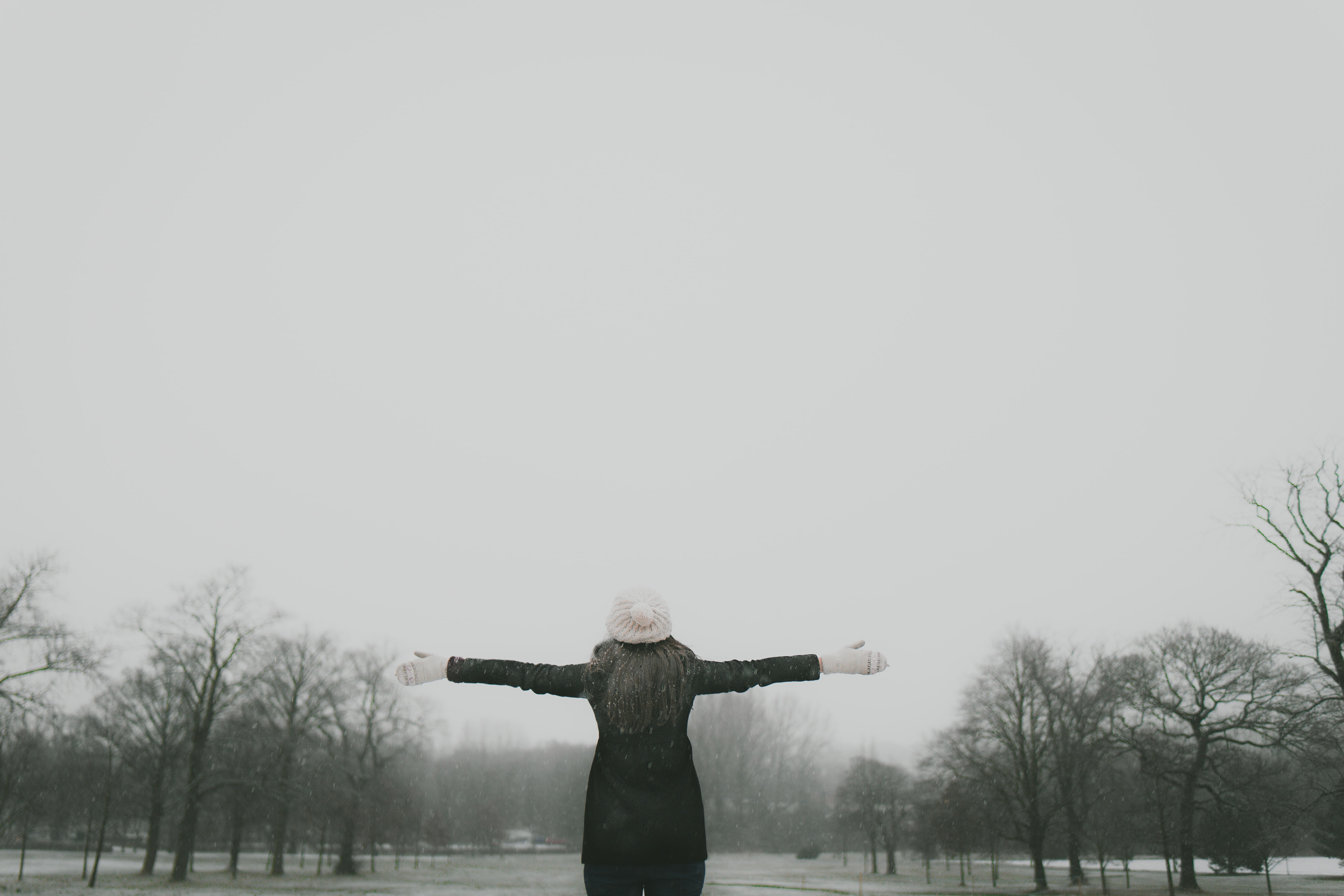 woman in black long-sleeved shirt standing and facing trees with stretched arms under white sky