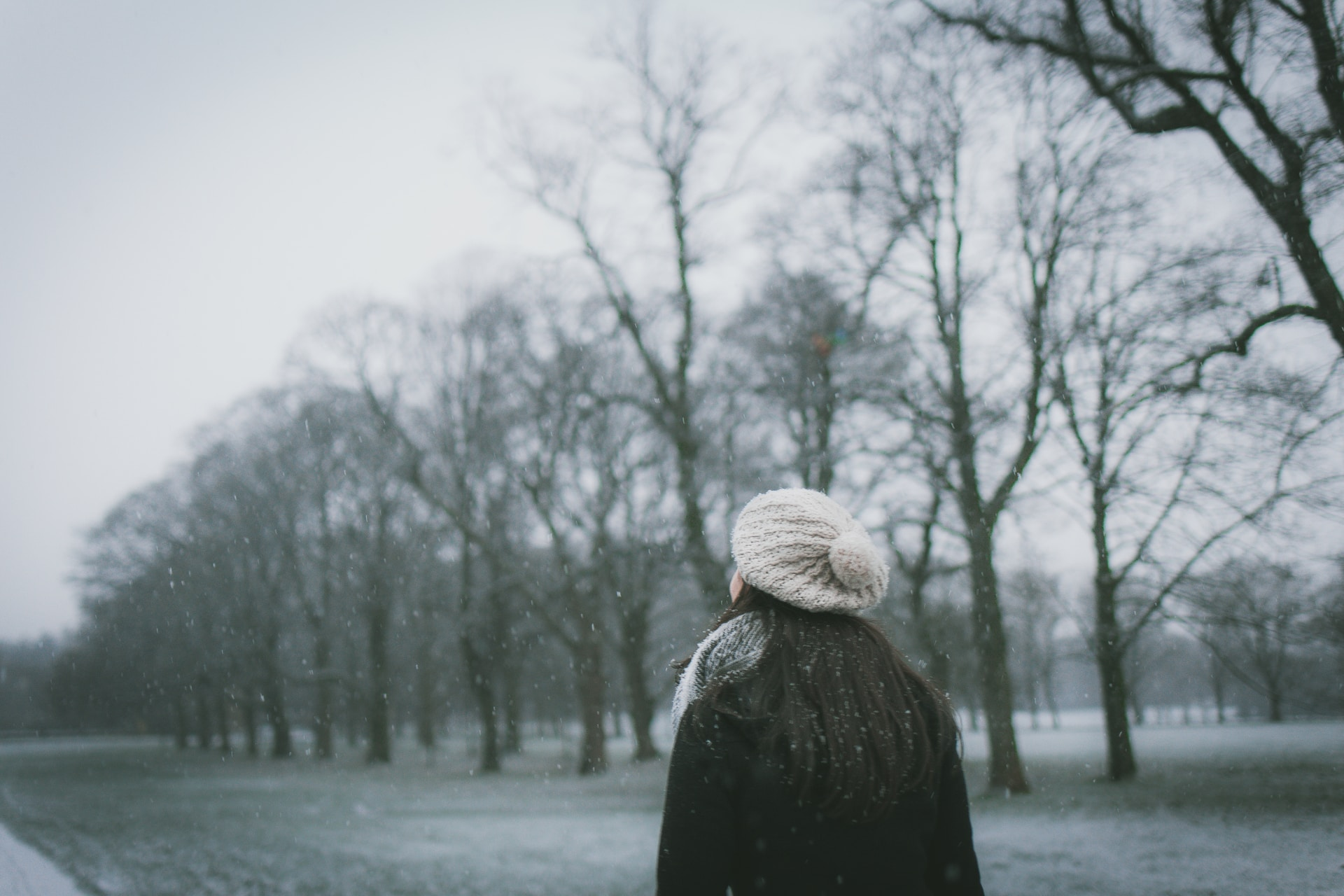 woman wearing cap and black coat standing near bare tree