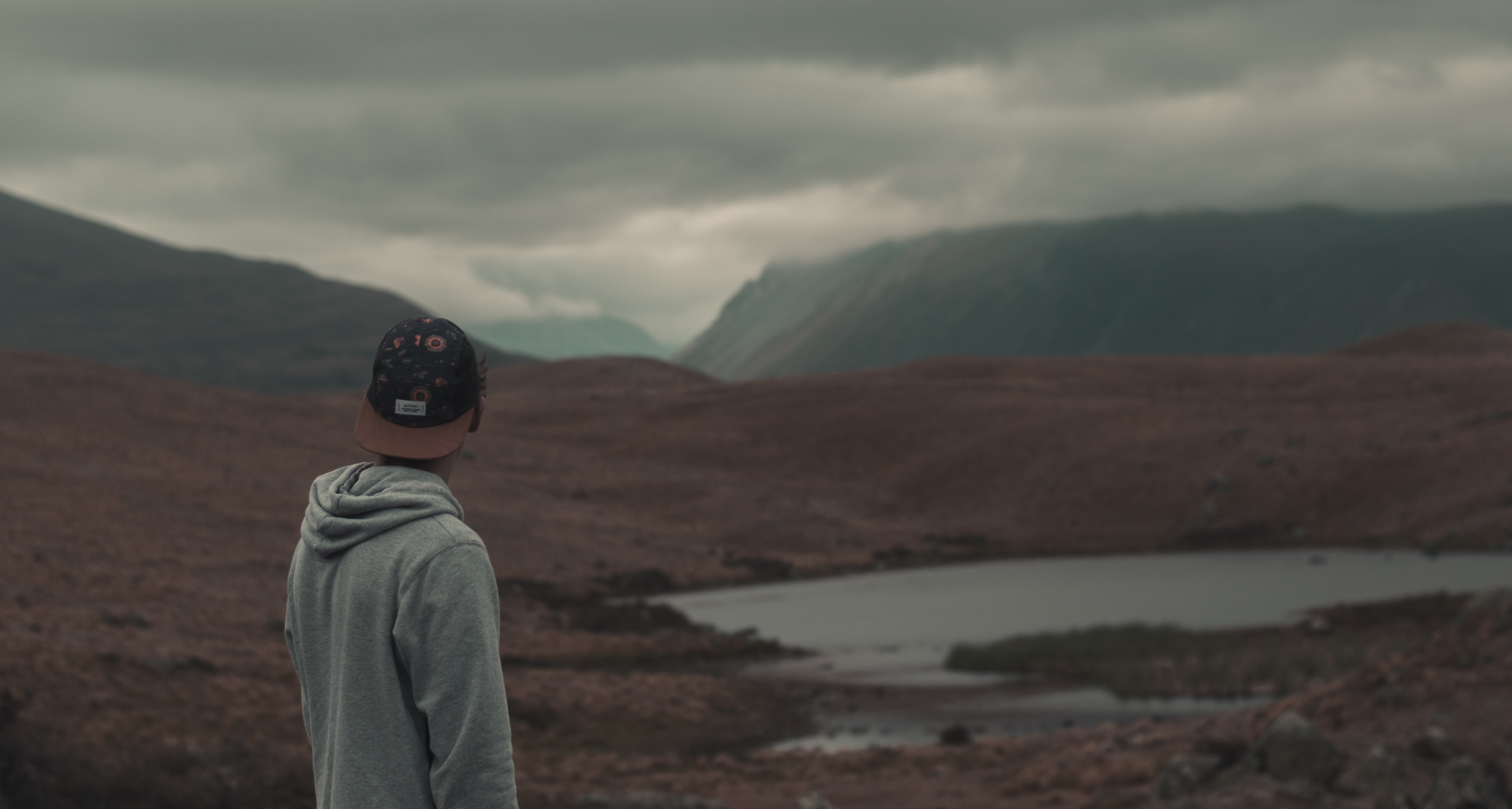 A man wearing a hat and a hoodie standing in front of Lake Alexandrina in a cloudy weather