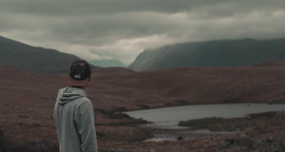 photo of man wearing gray hoodie and black cap