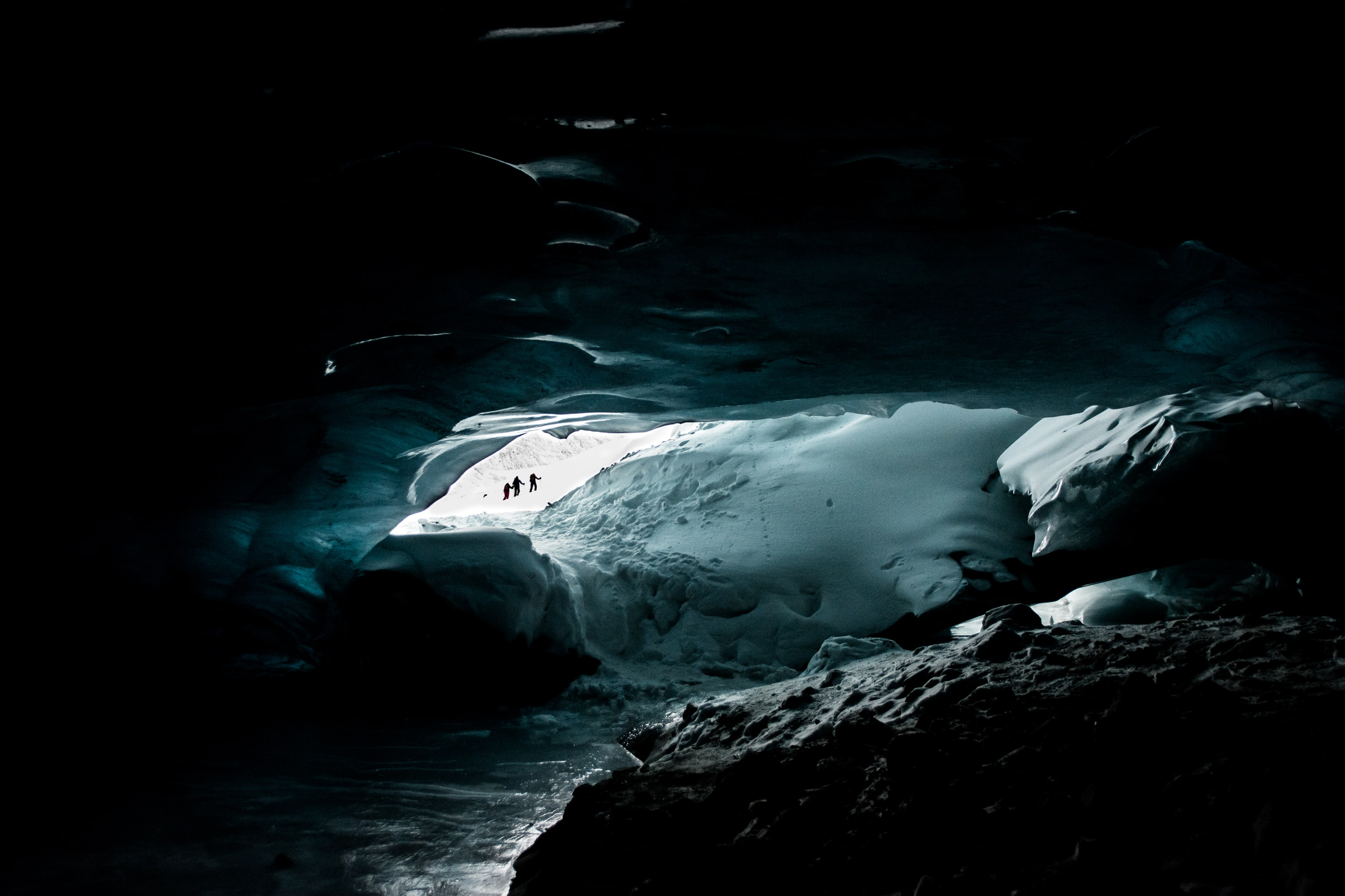 People in the opening of a cave filled with ice and snow