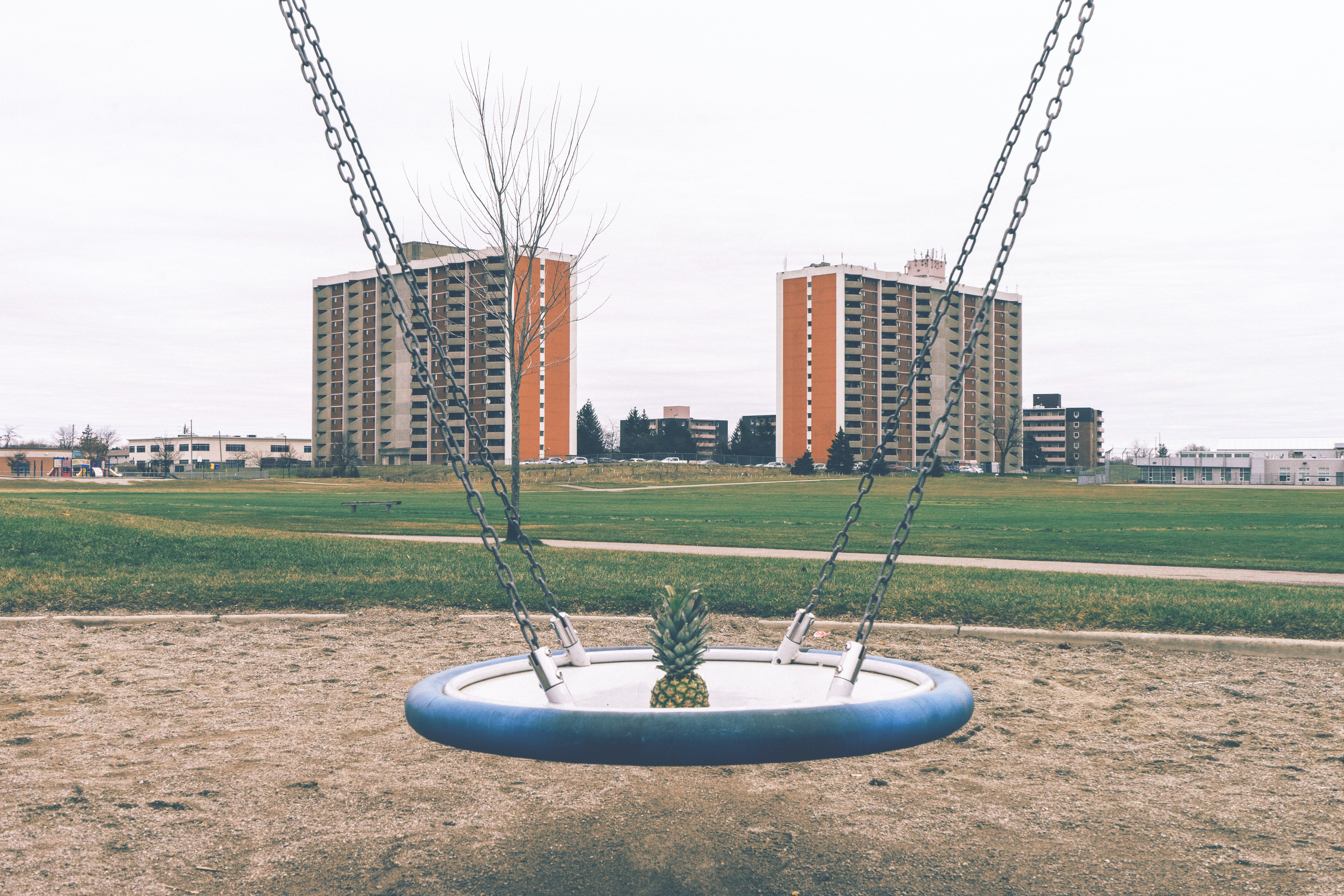 A pineapple in a swing in a playground with buildings behind it